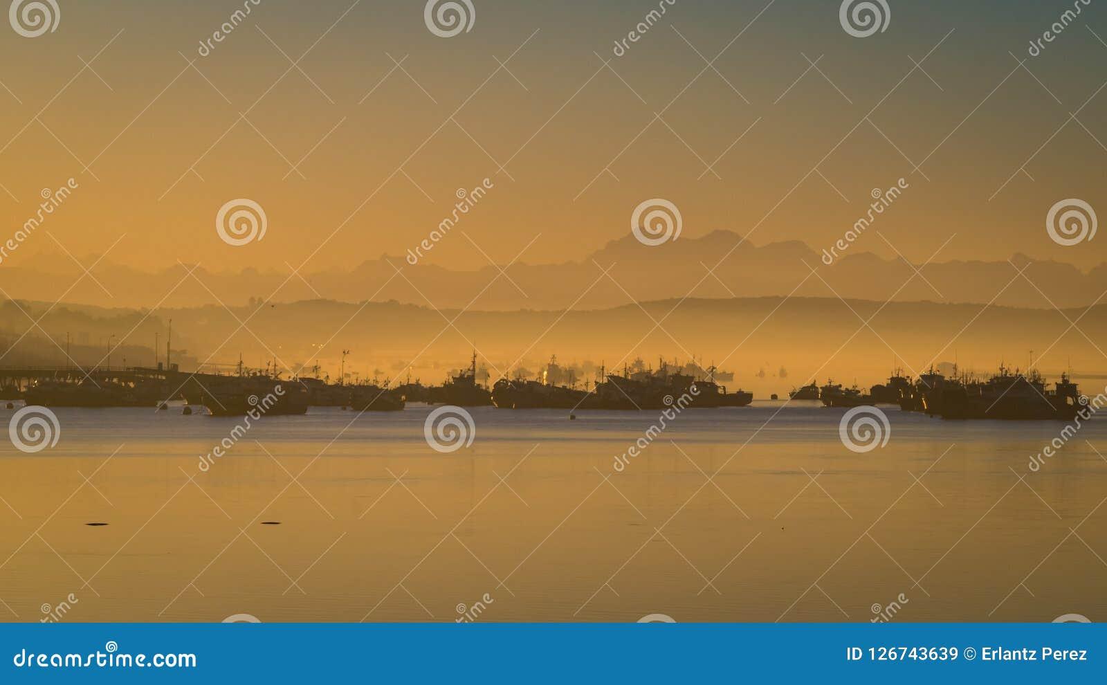 Sonnenaufgang im Hafen von Quellon in Chiloe-Insel Patagonia herein