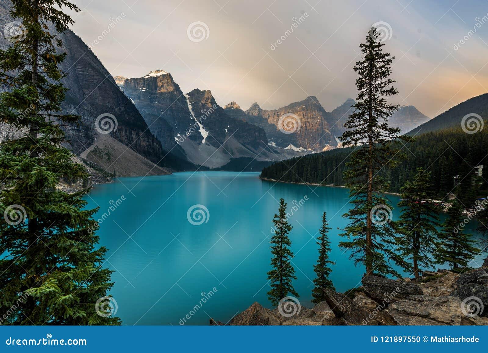 Sonnenaufgang mit Türkiswasser des Moraine Sees mit Sünde beleuchtete felsige Berge in Nationalpark Banffs von Kanada herein