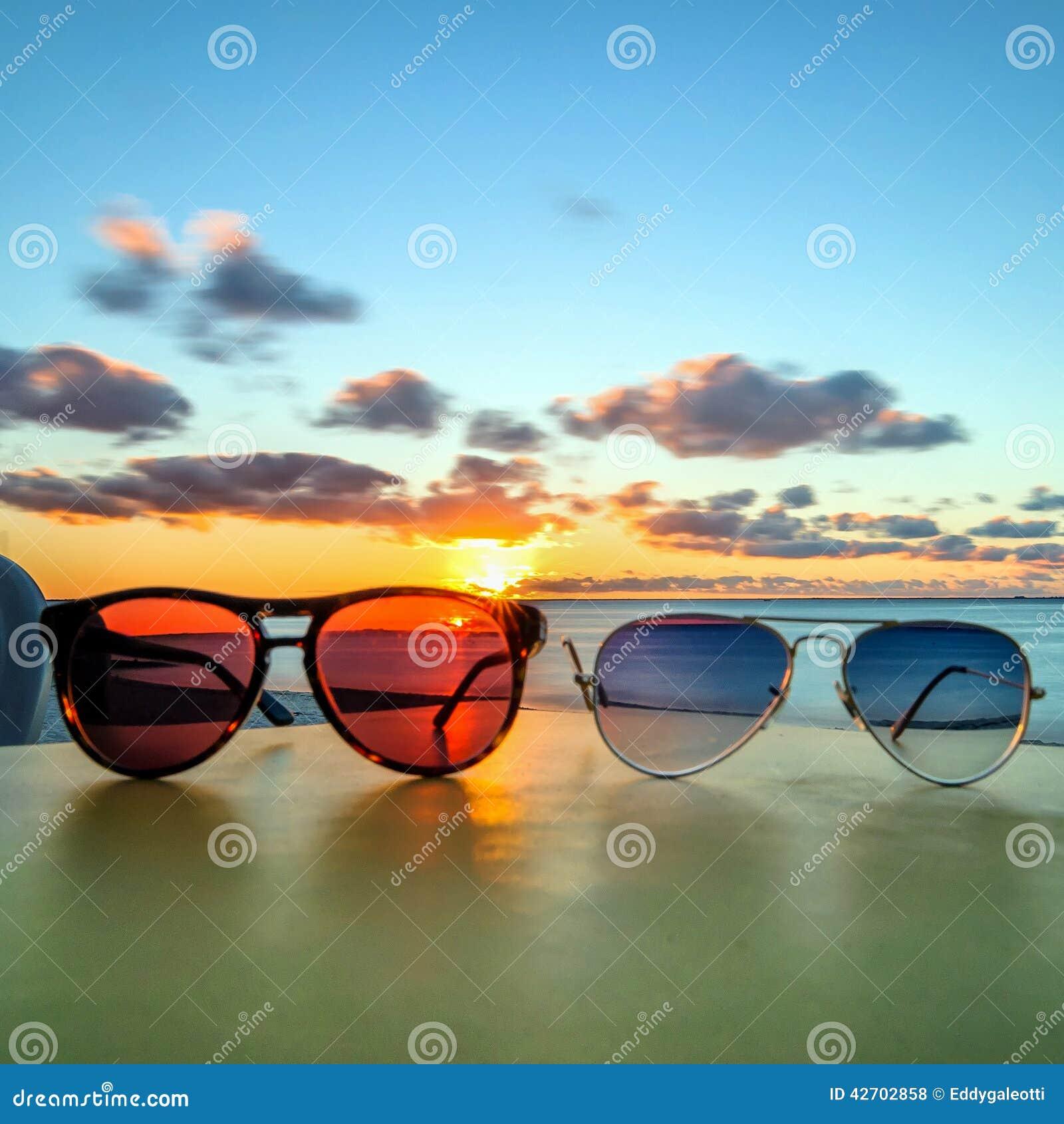 Sonnenbrille auf tropischer Strandtabelle bei Sonnenuntergang
