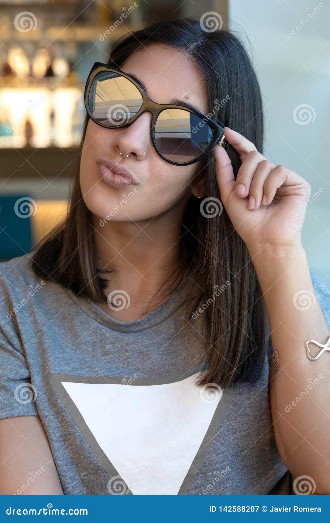 Sonnenbrillemädchen, das an der Kamera küsst