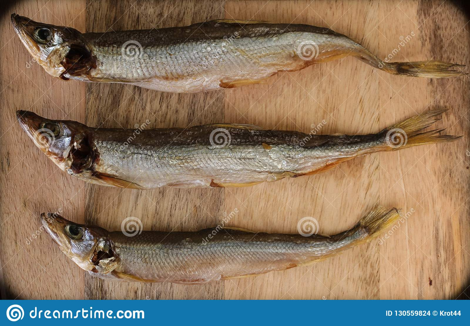 Sonnengetrocknete Fische, gesalzene Schmelze über hölzernem Hintergrund, Draufsicht, Kopienraum