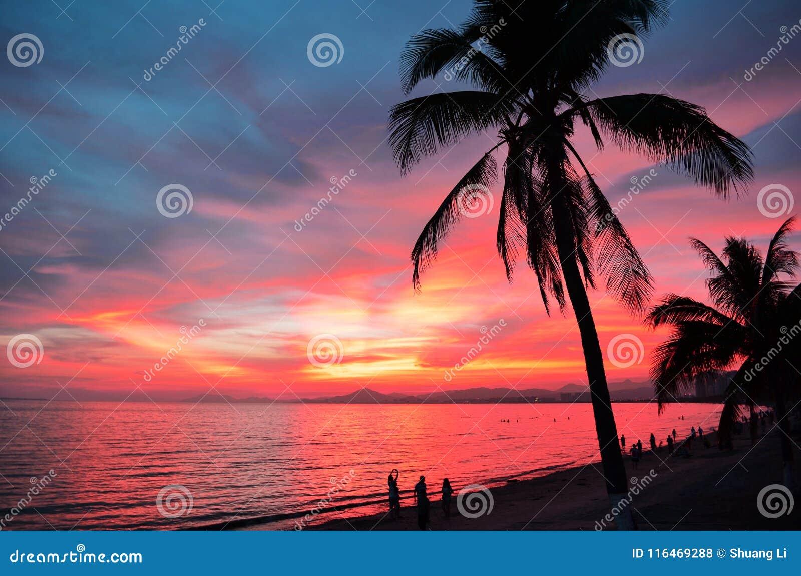 Sonnenuntergang über dem Meer mit Schattenbild von Palmen und von einigen Touristen am Strand im Abstand Sanya, China