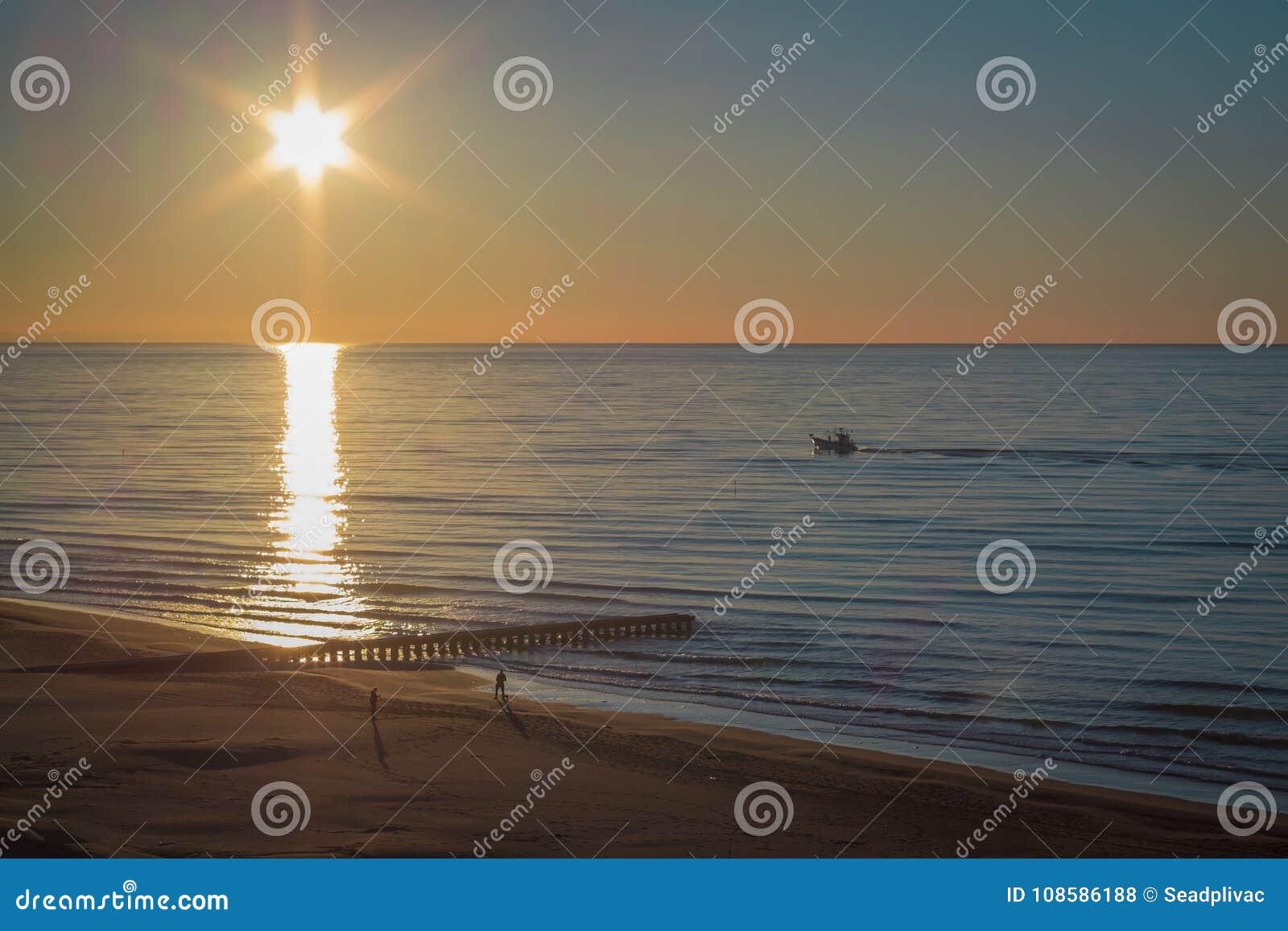 Sonnenuntergang auf einem sandigen Strand mit einem Dock