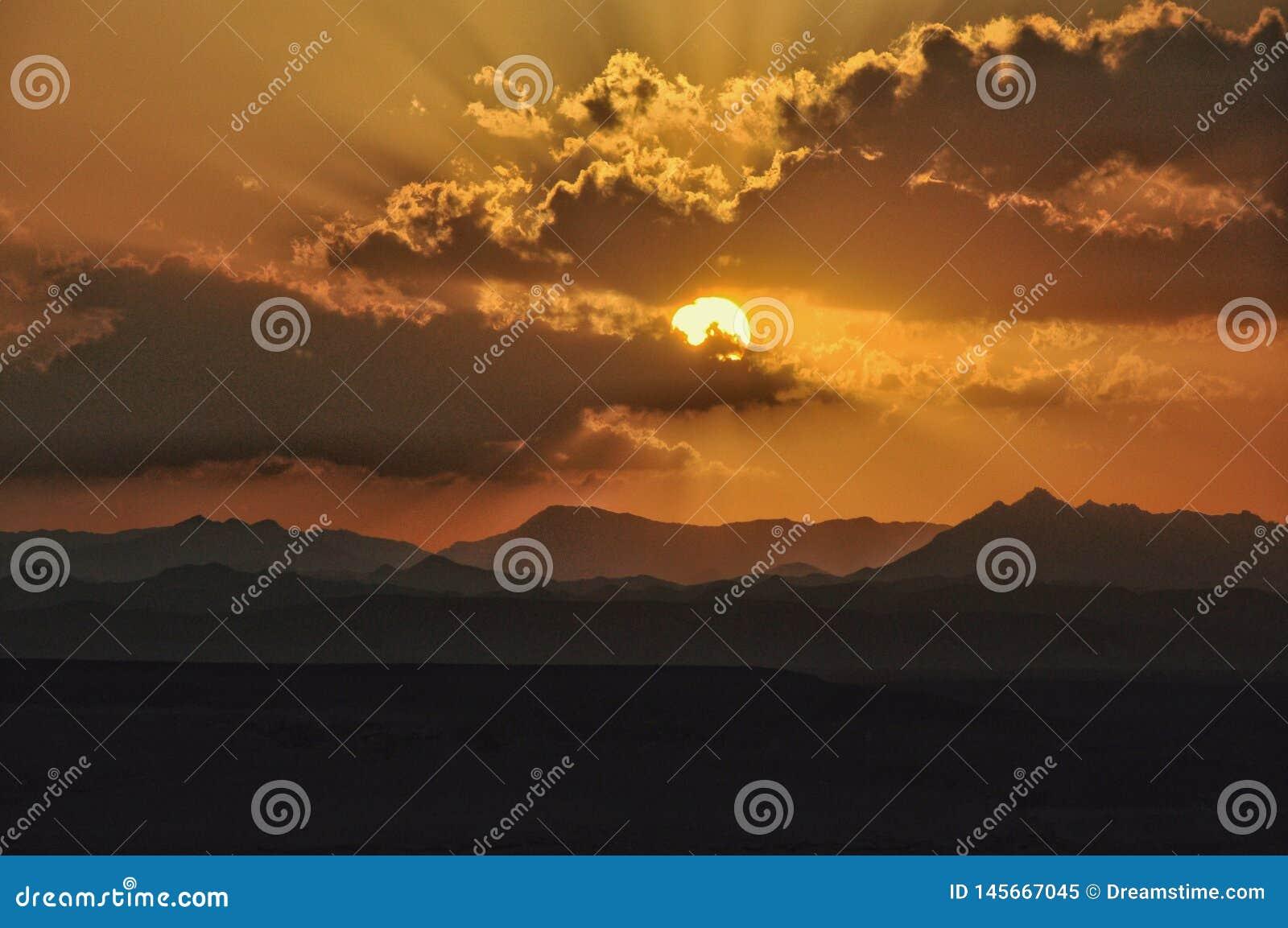 Sonnenuntergang ?ber den Bergen mit der Sonne, die durch die Wolken scheint