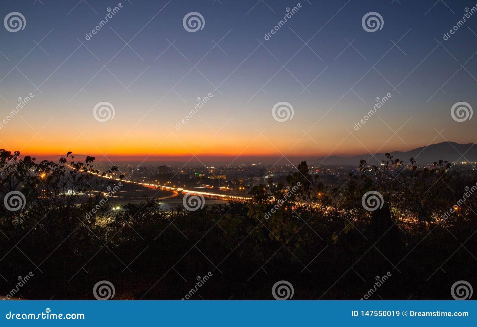 Sonnenuntergang mit beschäftigter Landstraße und Bergen im Abstand