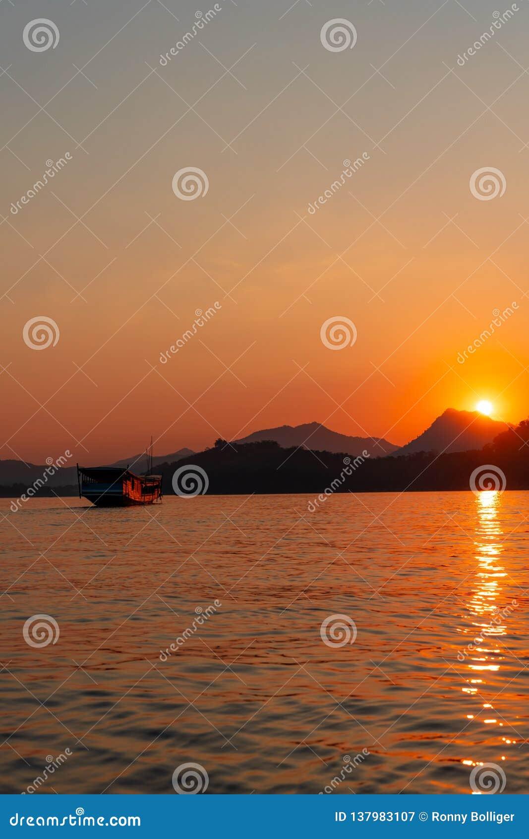 Sonnenuntergangkreuzfahrt in Luang Prabang auf dem Mekong Himmel brennt als die Sonne, welche die Berge schlägt