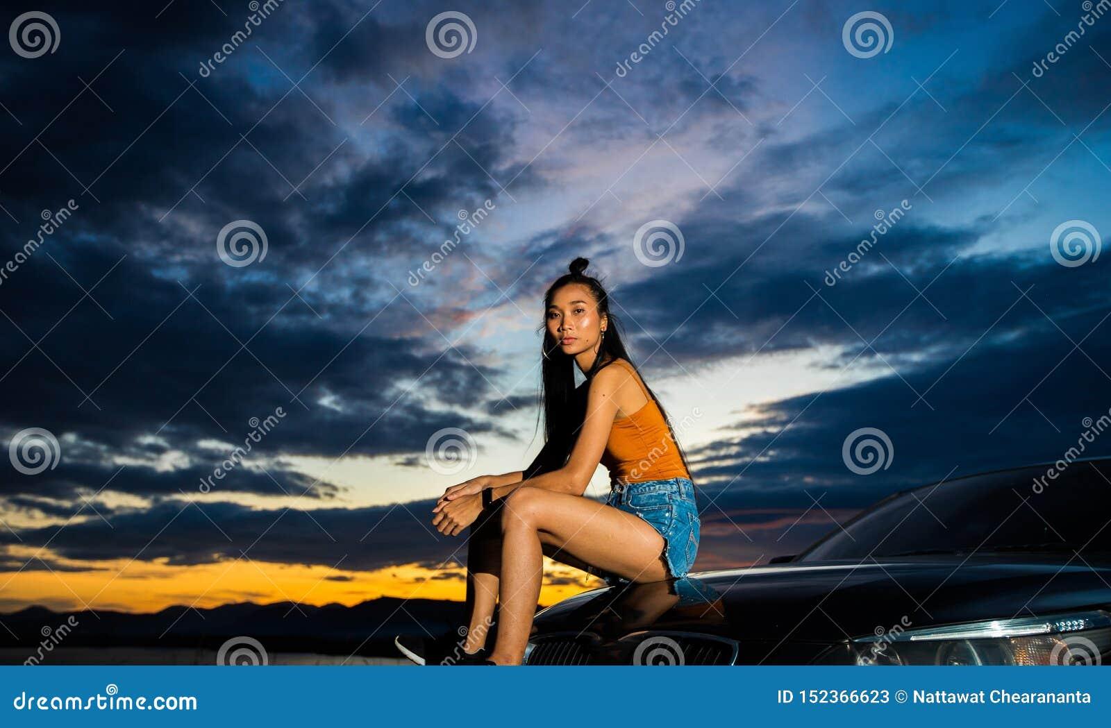 Sonnenuntergangwolkenstrahl zum jungen erwachsenen asiatischen woma