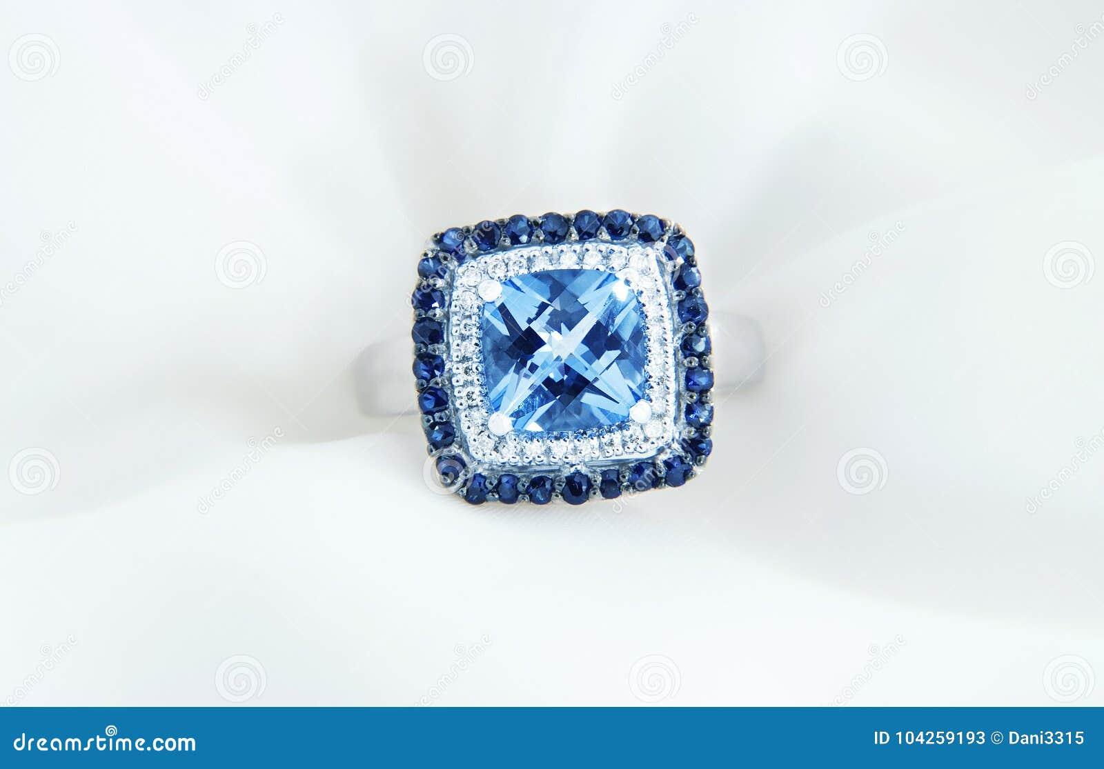 Sonnez avec la topaze et les diamants bleus sur le fond blanc mou