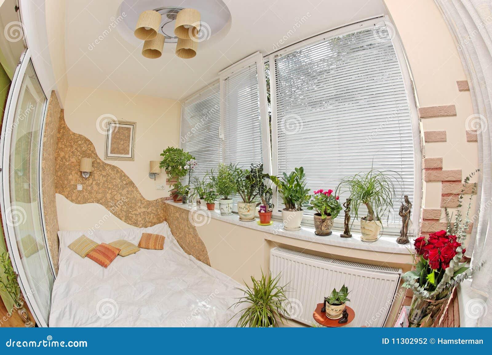 Sonniges Schlafzimmer auf Balkon mit Fenster und Anlagen
