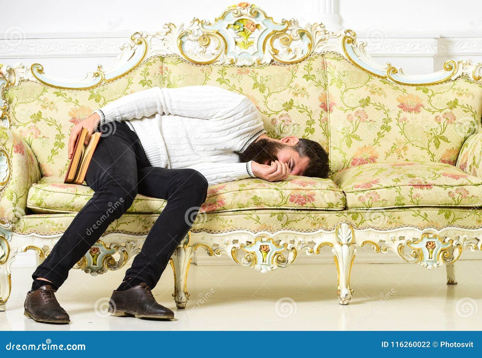 Sonno macho con il libro a disposizione Concetto noioso della letteratura L uomo con la barba ed i baffi mettono sul sofà barrocc