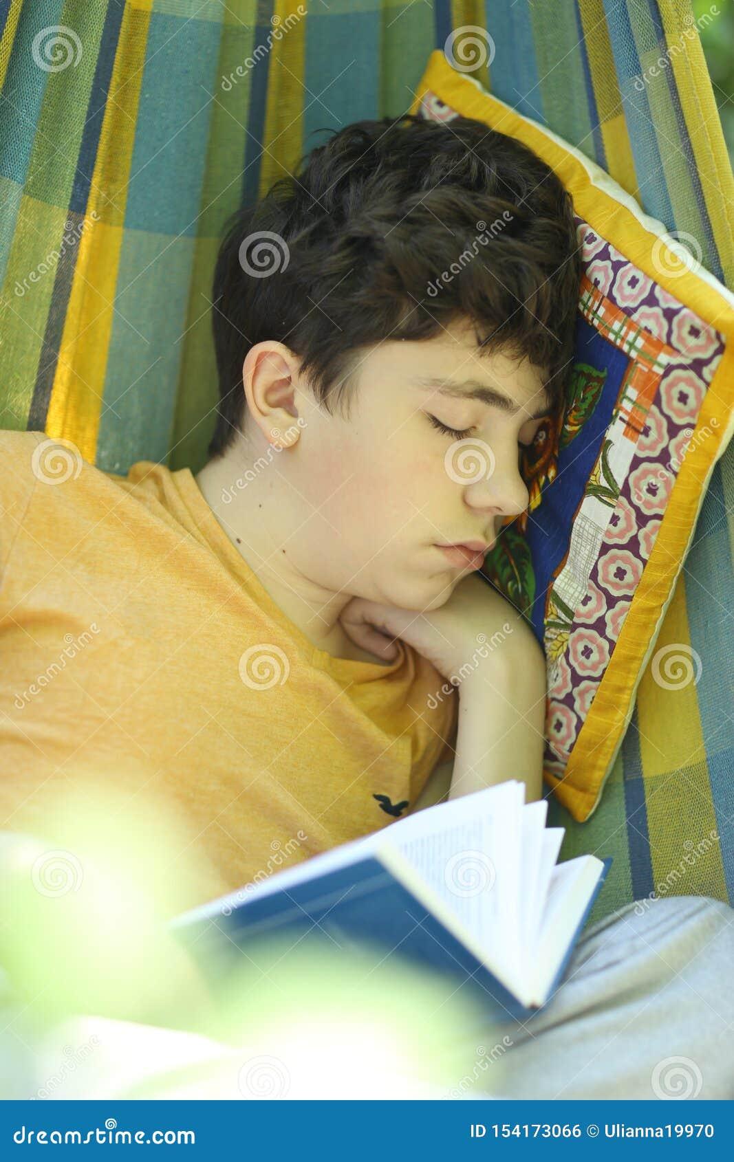 Sono de descanso do menino do adolescente com o livro na rede no jardim verde do verão
