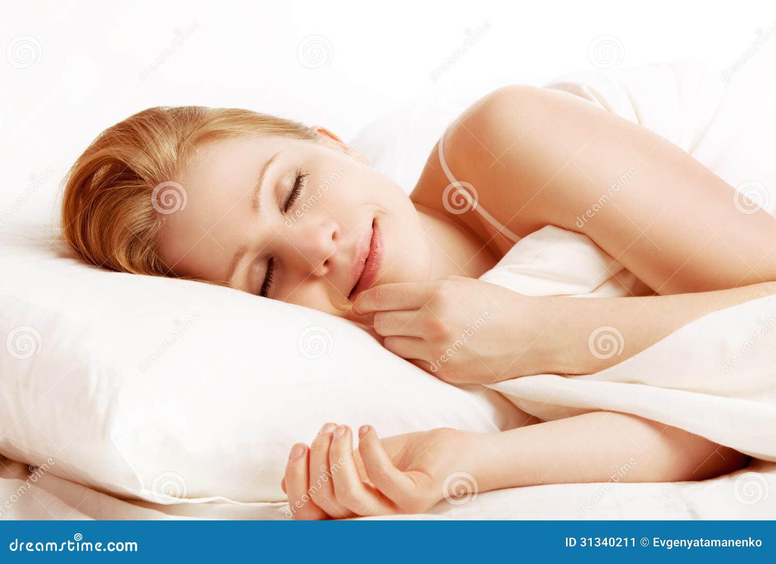 Sono e sorrisos bonitos da mulher no seu sono na cama