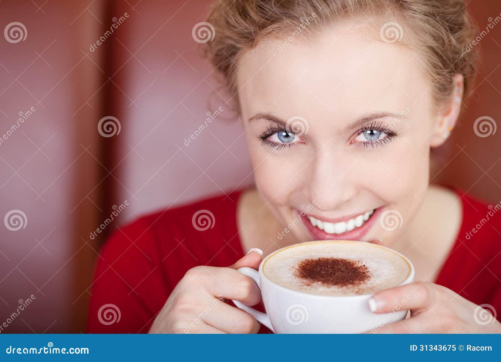 Sonriendo, capuchino de consumición de la mujer hermosa