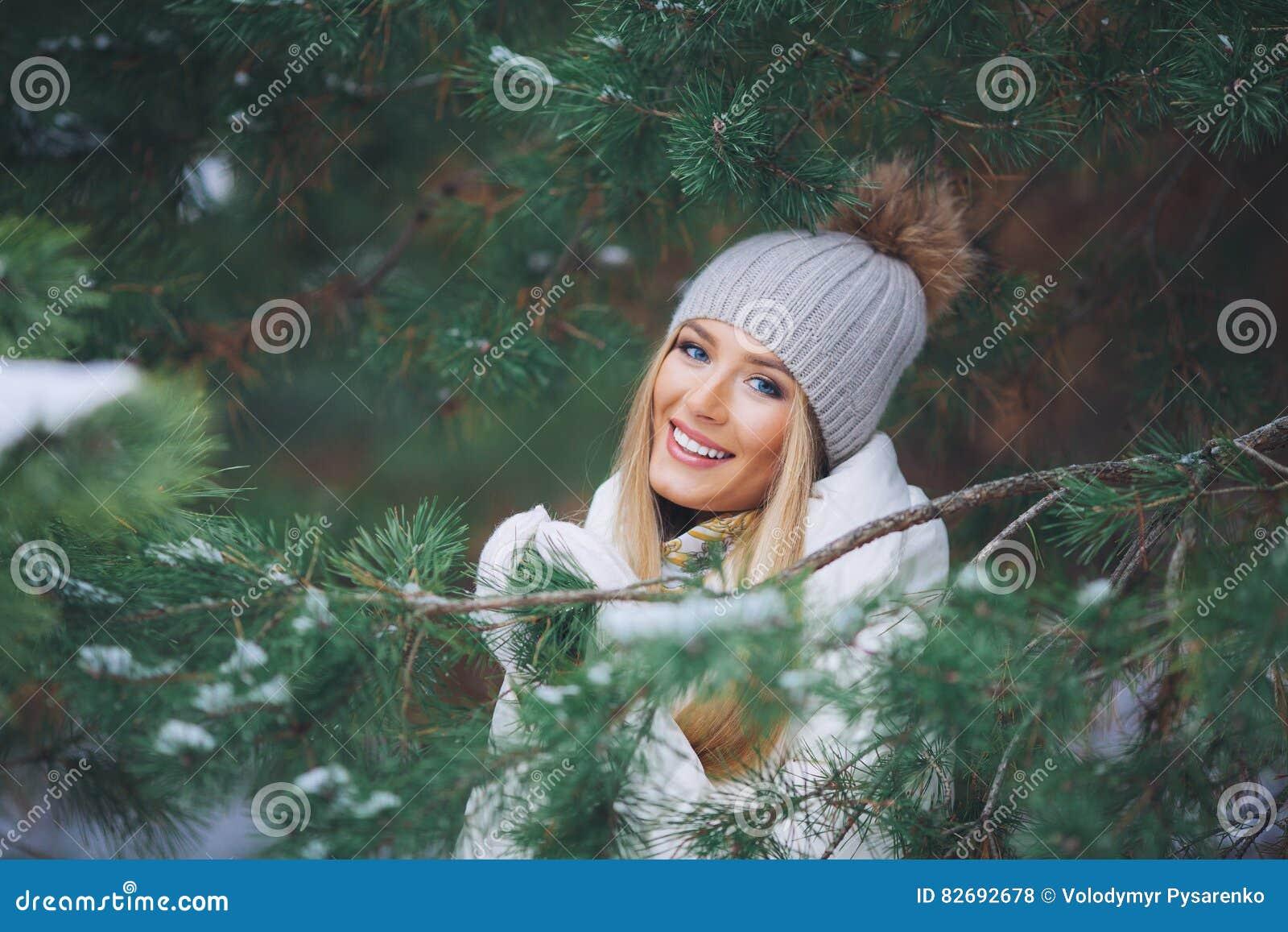 Sonriendo, chica joven feliz que camina en bosque del invierno