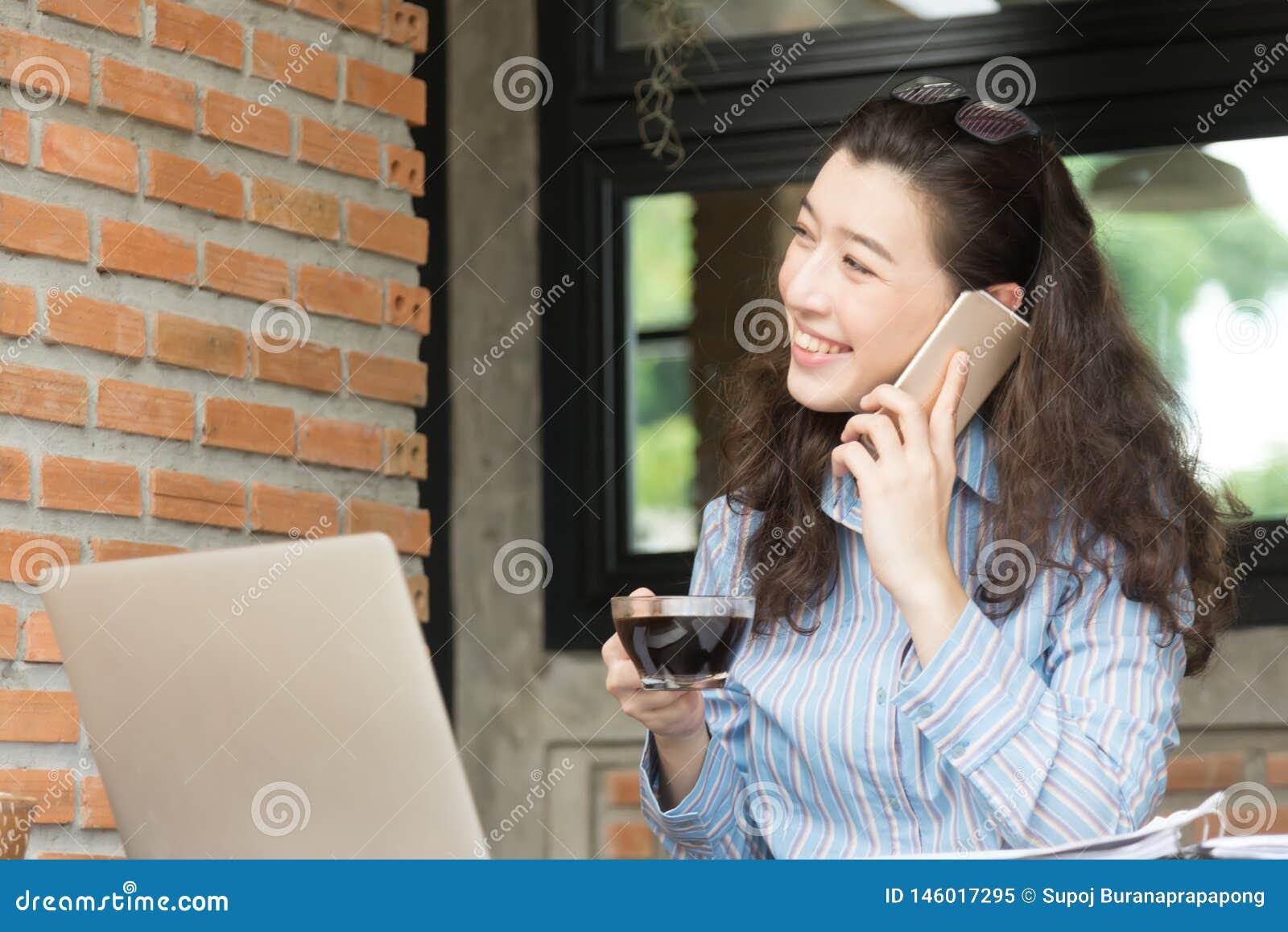 Sonrisa alegre joven de la mujer de negocios que se sienta en el caf? de la terraza, disfrutando de la comunicaci?n en l?nea usan