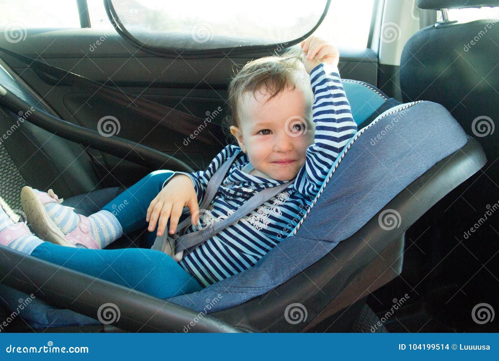 Sonrisa del bebé en un asiento de carro de la seguridad Seguridad la muchacha de un año del niño en desgaste azul se sienta en cu