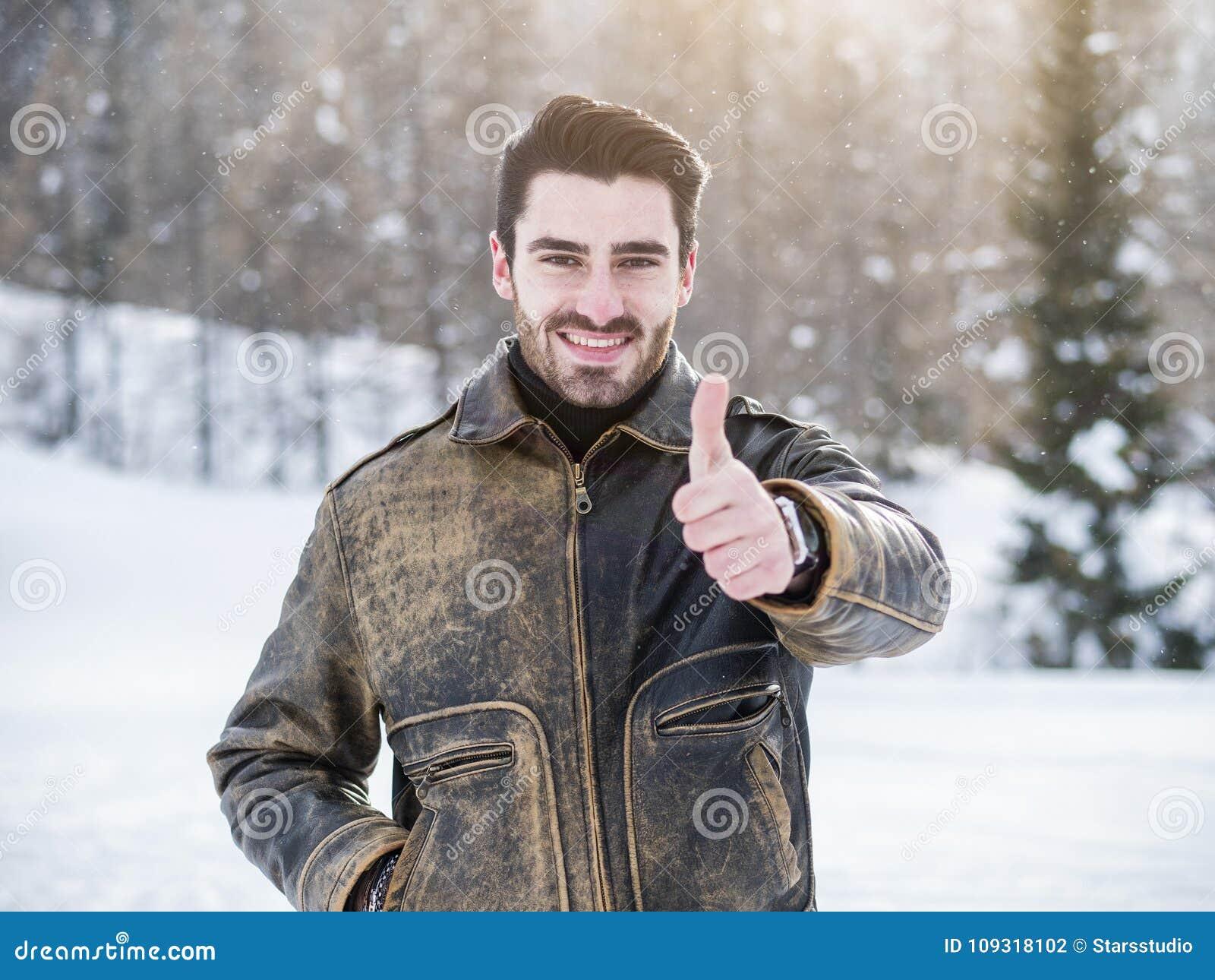Sonrisa feliz atractiva del hombre joven, haciendo el pulgar encima de la muestra