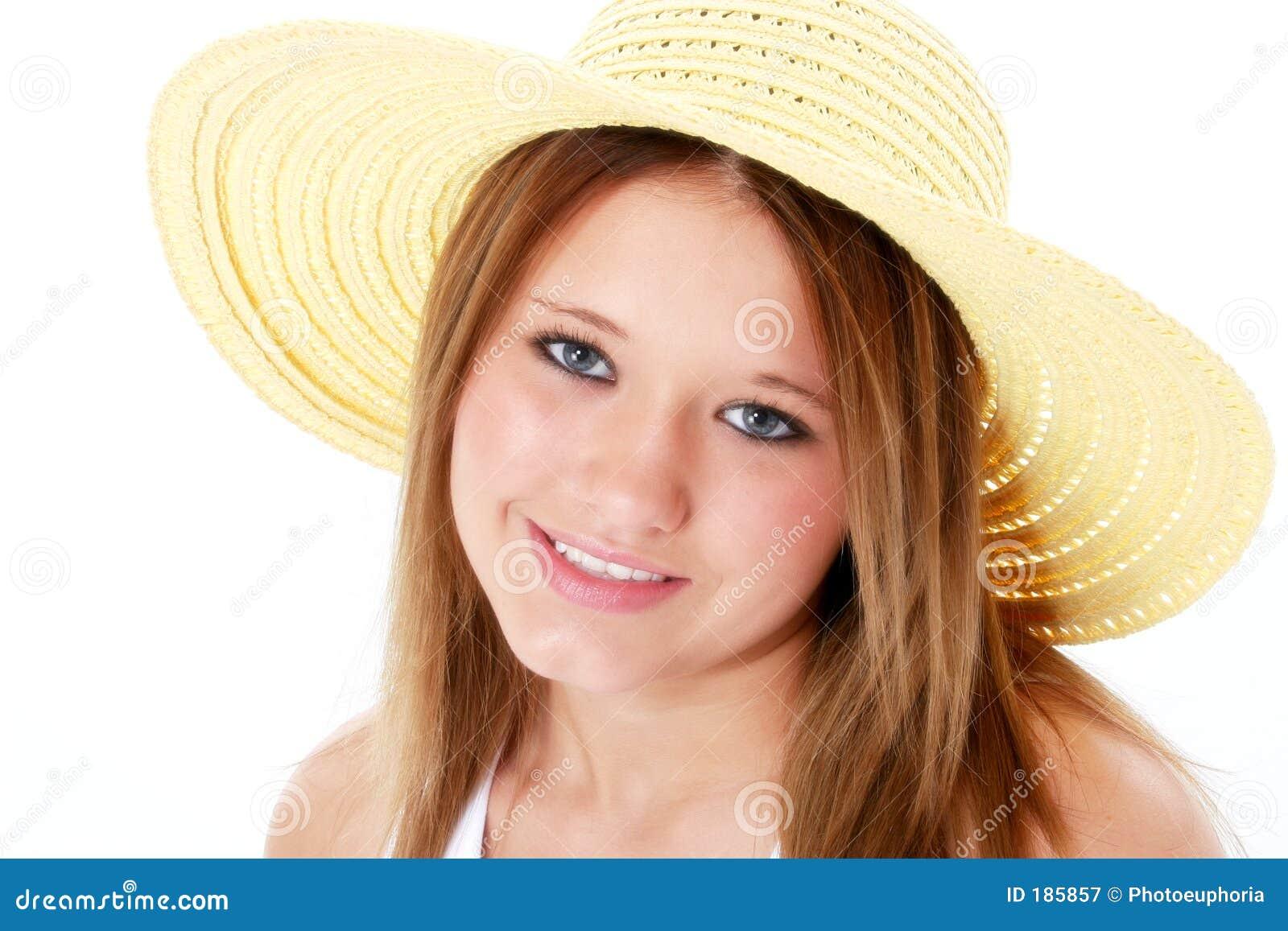 Sonrisa hermosa adolescente en sombrero amarillo sobre blanco