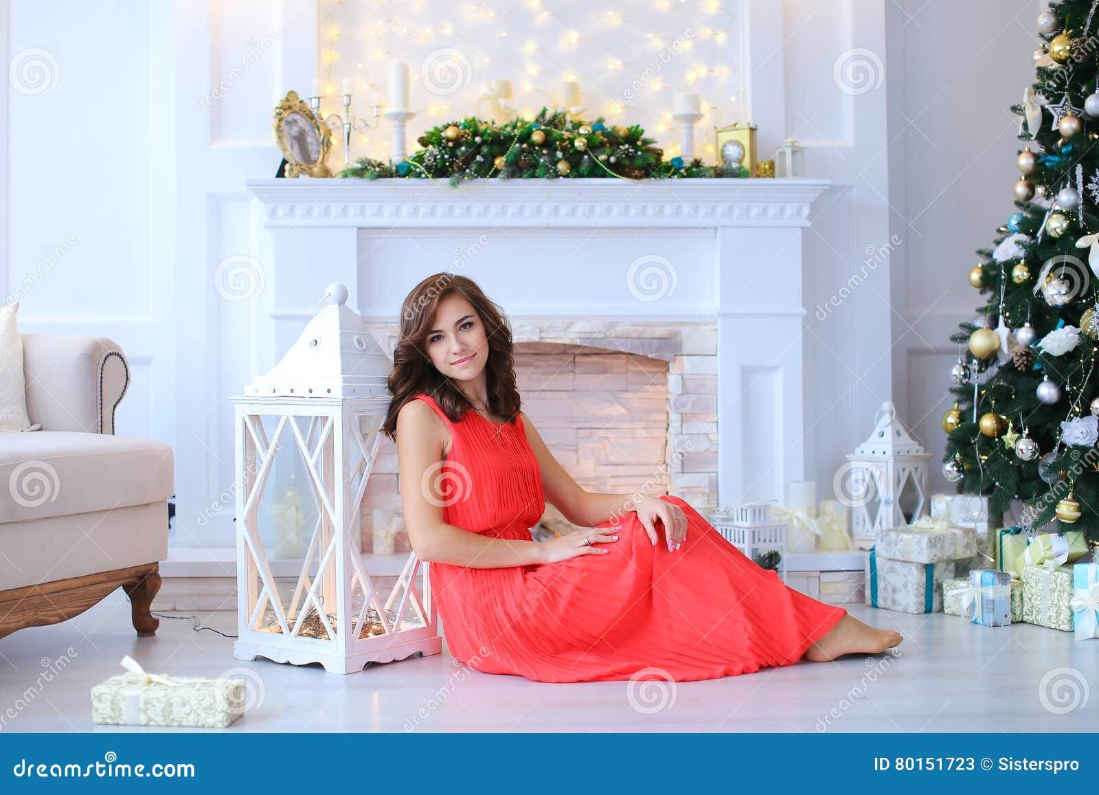 Sonrisa hermosa joven de la muchacha, sentándose en piso cerca de la linterna en s