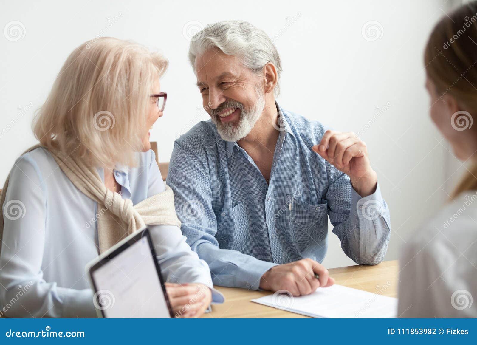 Sonrisa que habla de la familia mayor feliz en la reunión con el anuncio financiero