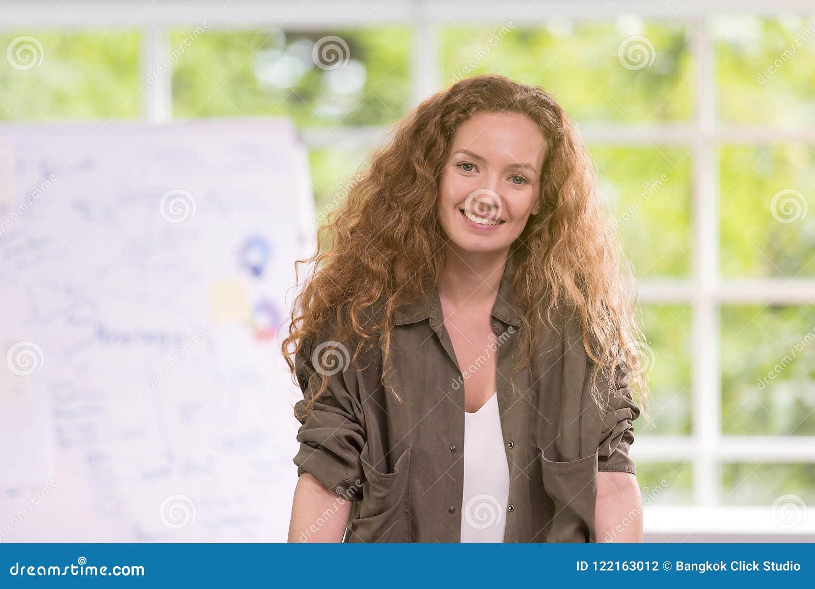 Sonrisa rizada del pelo rubio de la empresaria hermosa feliz con un re