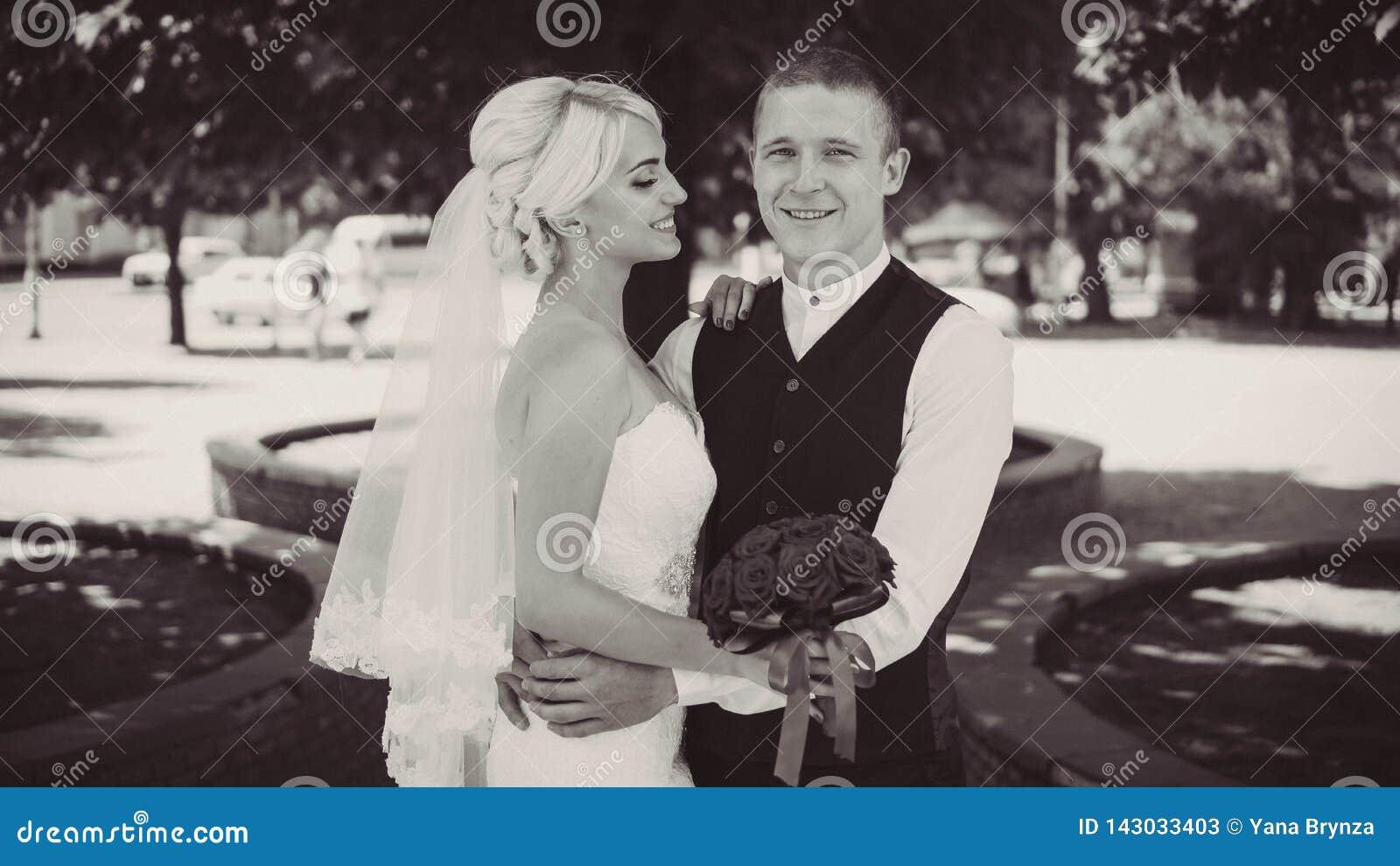 Sonrisas jovenes alegres de la novia cuando ella se coloca con su marido Pares casados Marido y esposa Primer Rebecca 36