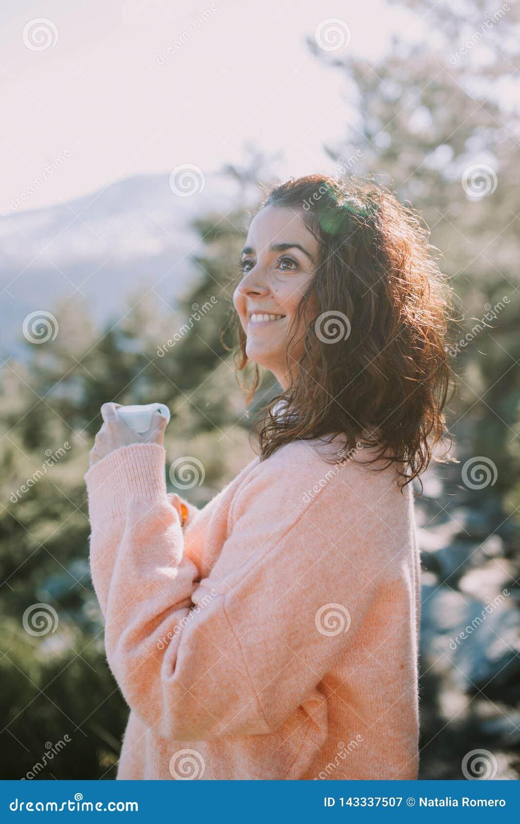 Sonrisas morenas de la muchacha feliz como ella ase una botella de agua y de miradas en el paisaje hermoso delante de ella