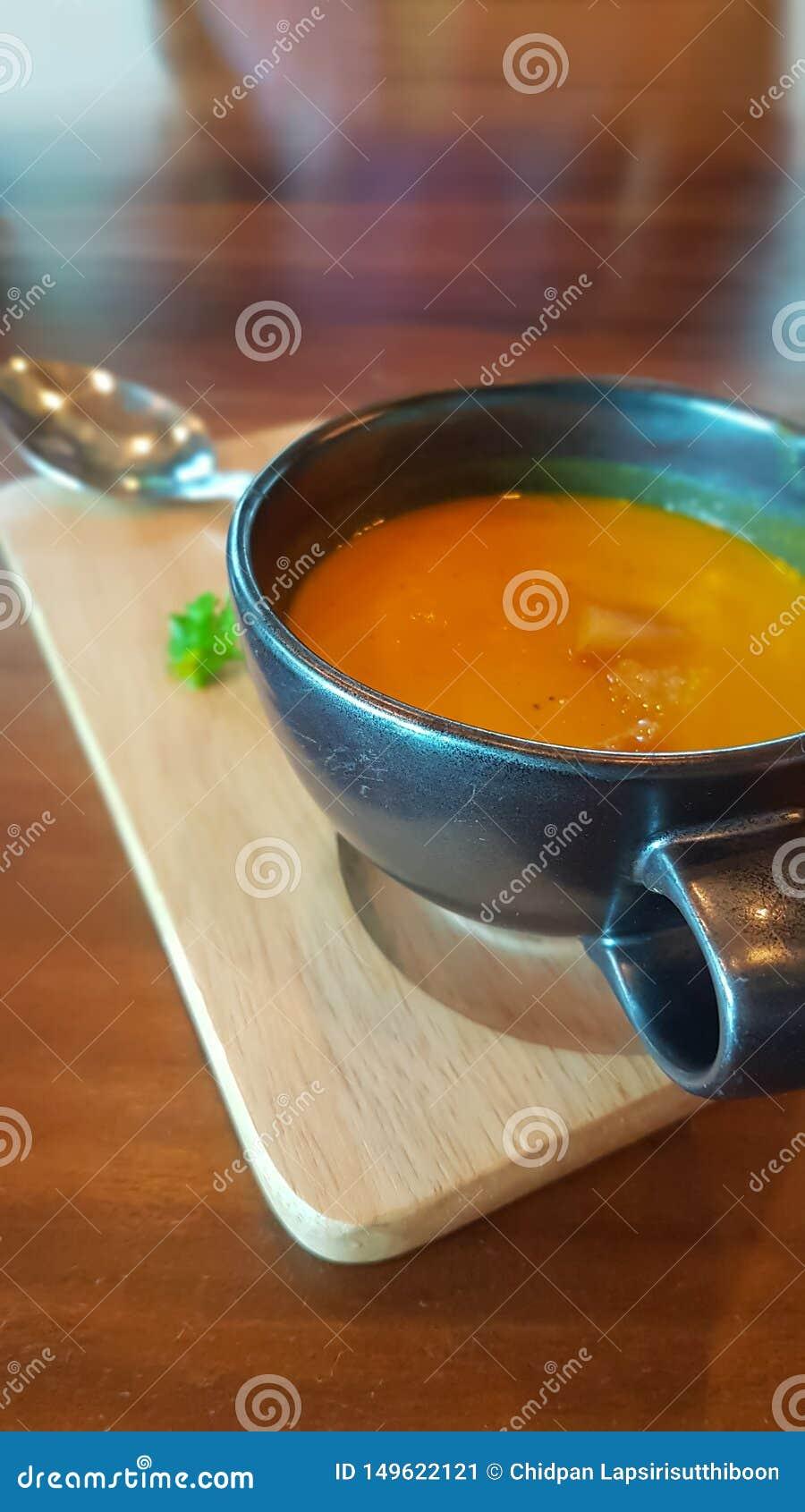 Sopa amarela da ab?bora em uns copos pretos da sopa