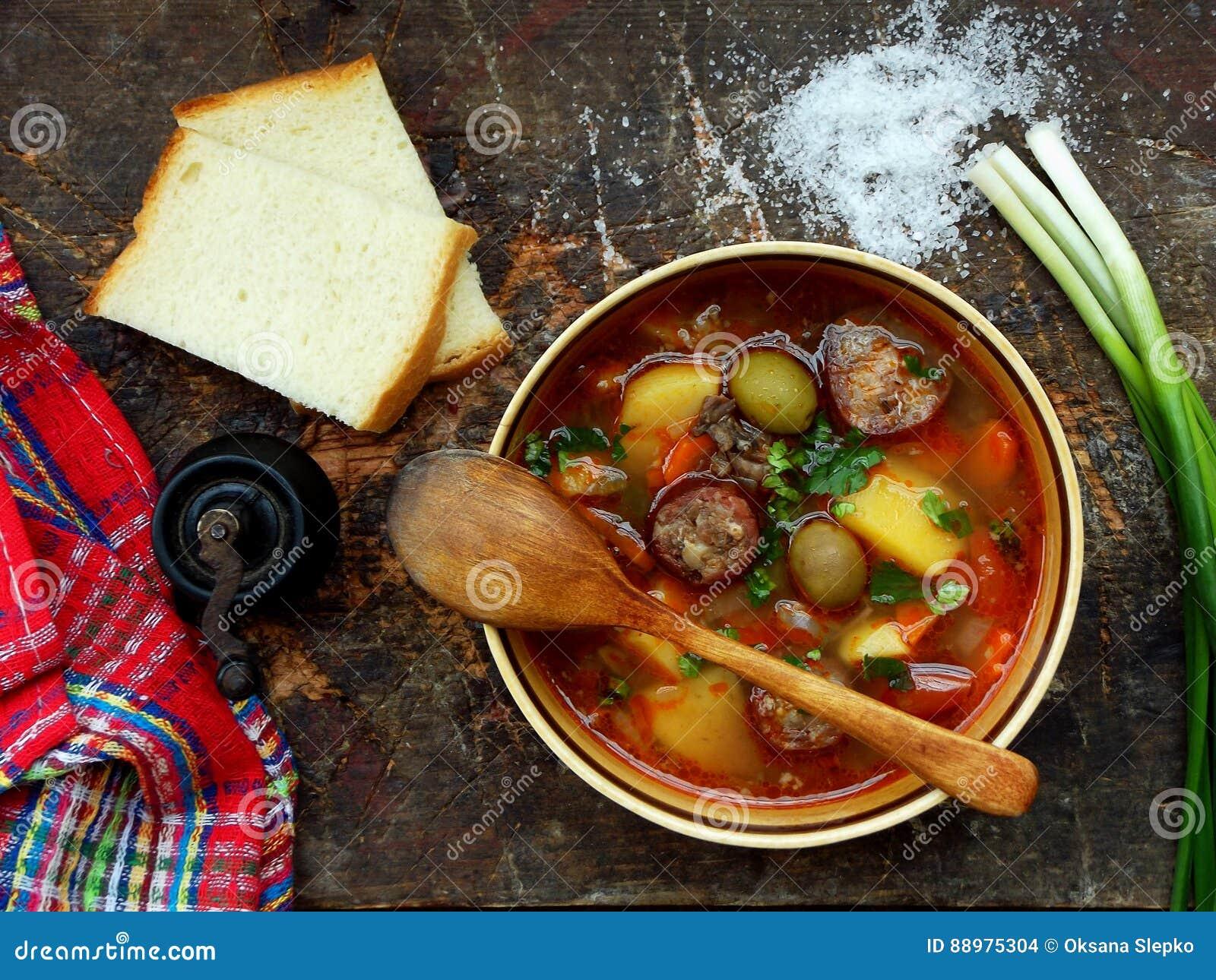 A sopa caseiro entusiasta com batatas, as cenouras, as salsichas e as azeitonas em uma argila rolam em um fundo de madeira