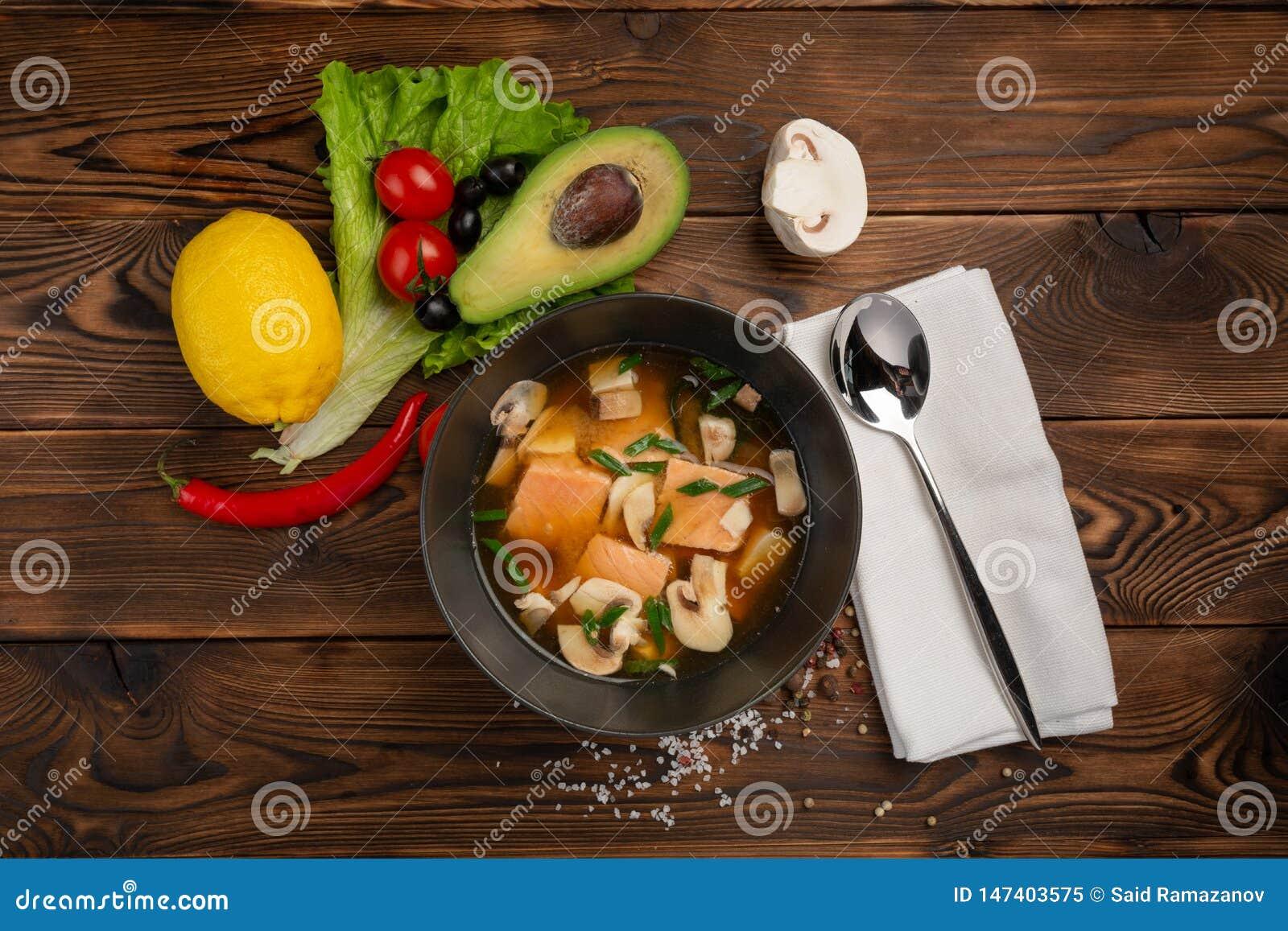 Sopa china con los pescados rojos en una placa negra en un fondo de madera