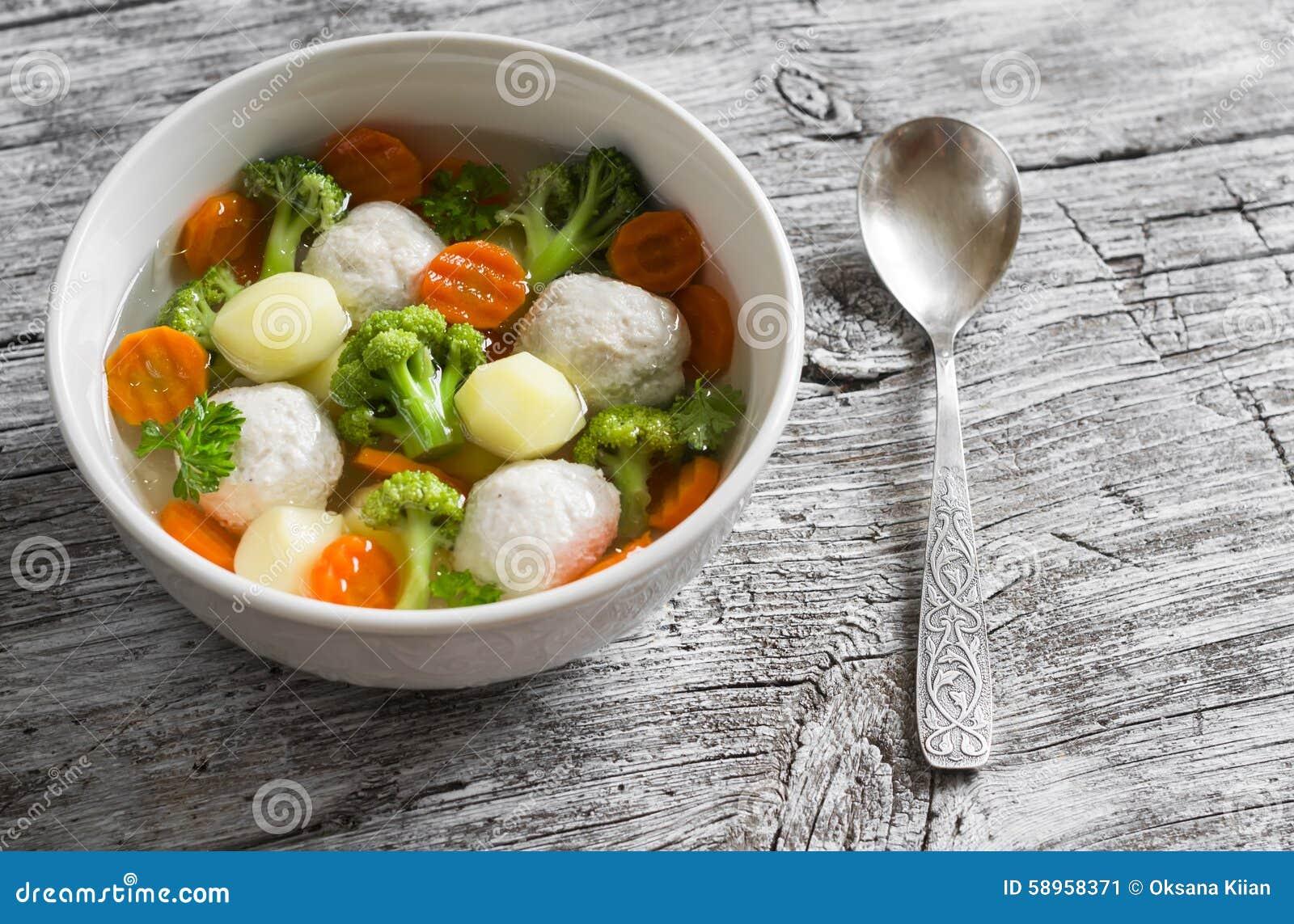 Sopa con las bolas de carne del pollo, las patatas, el bróculi y las zanahorias en un cuenco blanco