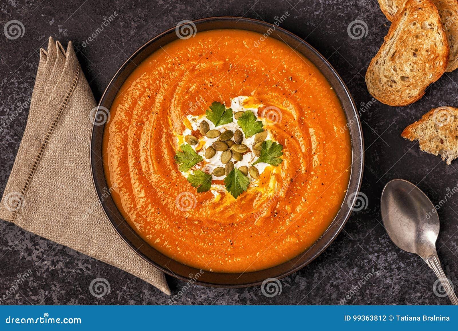 Sopa da abóbora e da cenoura com creme, sementes e salsa