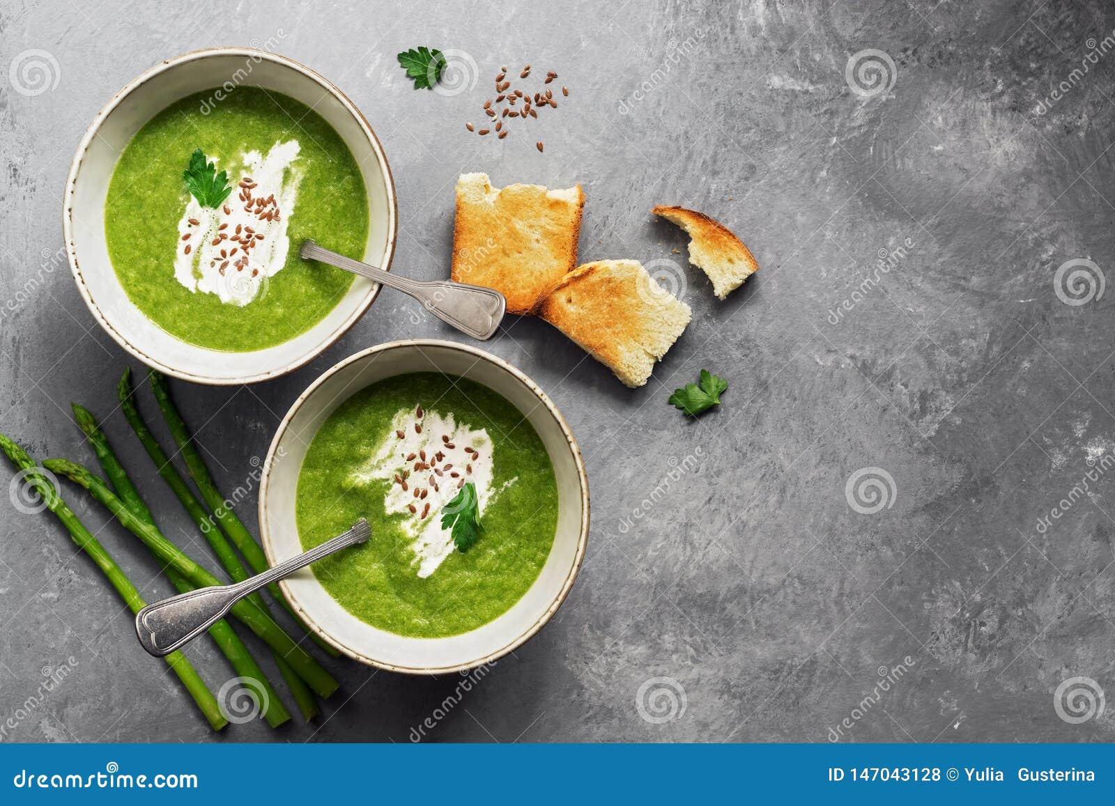 Sopa de creme verde do aspargo com brindes friáveis em um fundo cinzento Vista a?rea, espa?o da c?pia
