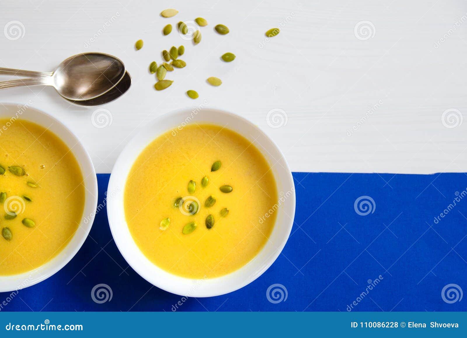 Sopa de las semillas de la calabaza y de girasol en una placa blanca con las cucharas de plata en un fondo brillante El concepto