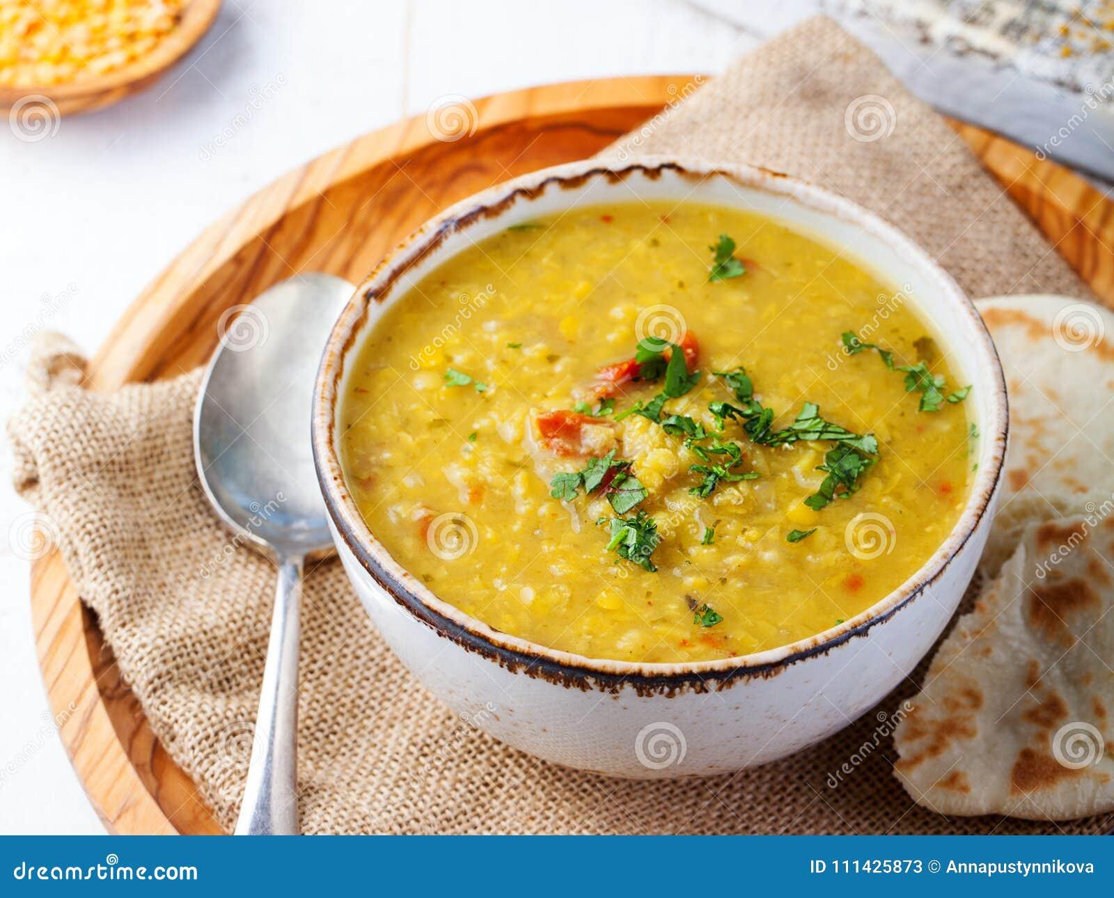 Sopa de lentilha com pão do pão árabe em uma bacia branca cerâmica em um fundo de madeira Fim acima