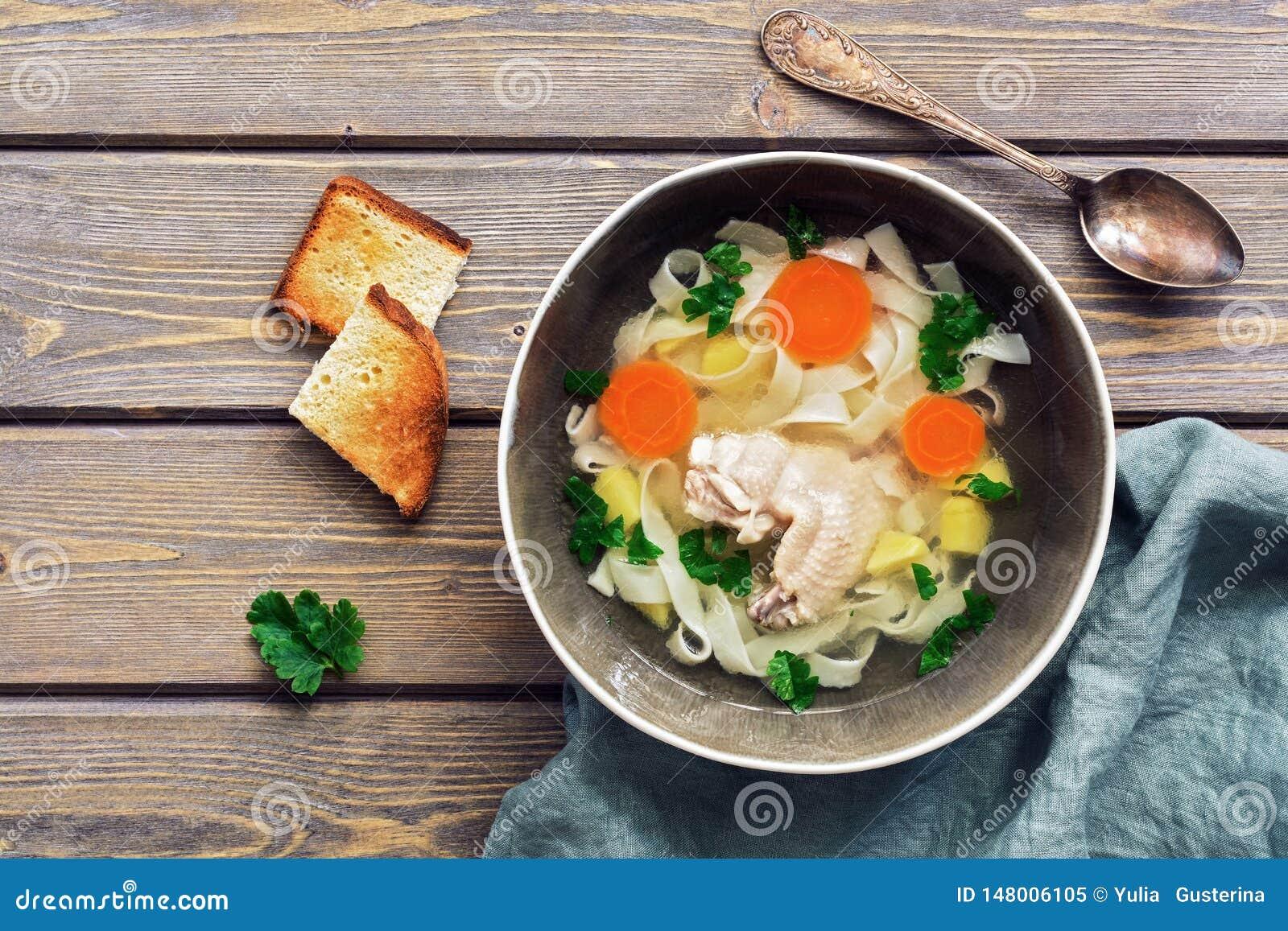 Sopa de macarronete caseiro da galinha em uma tabela rústica de madeira da prancha Vista superior, espa?o da c?pia