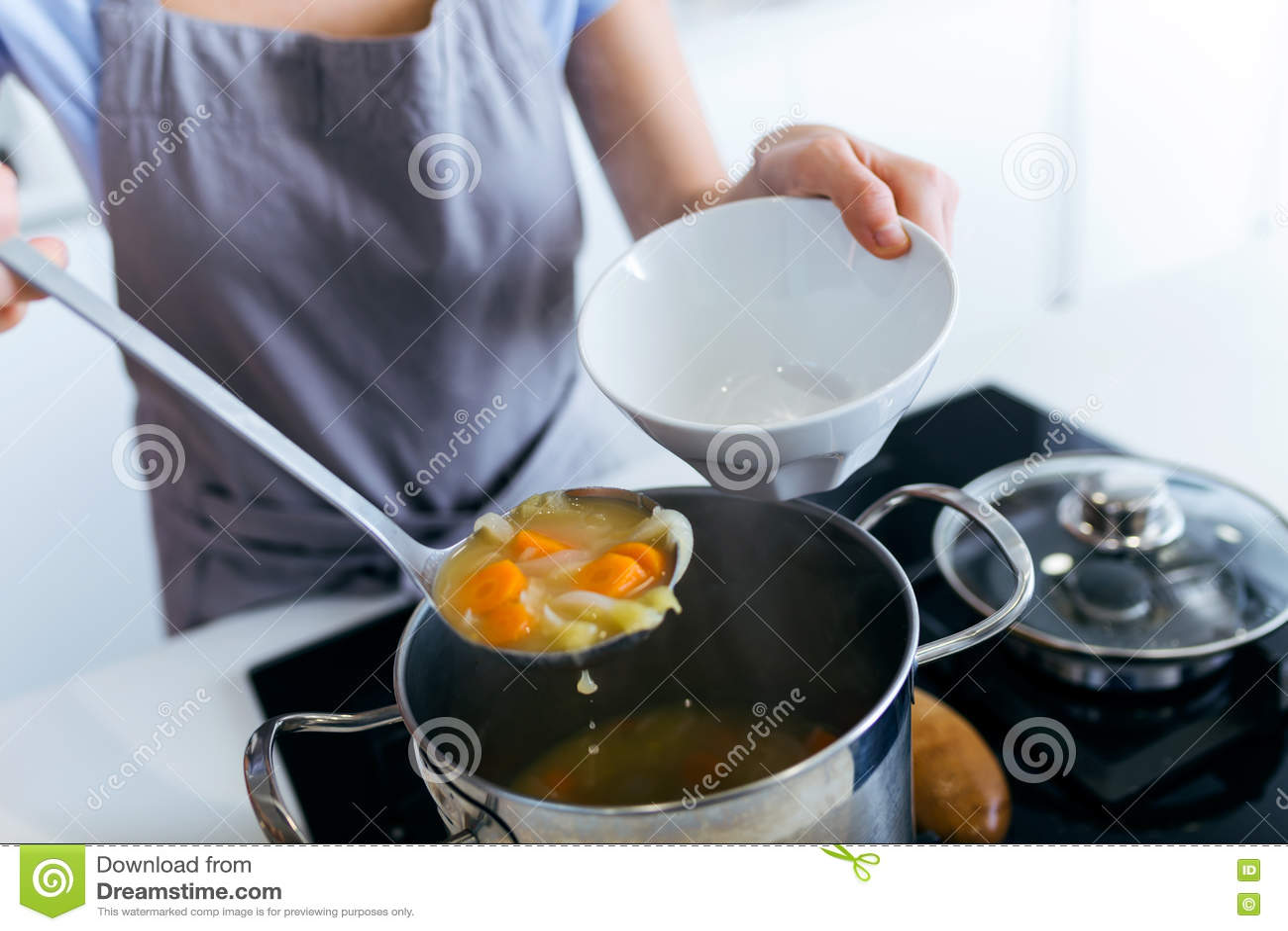 Sopa de verduras de la porción de la mujer joven en la cocina