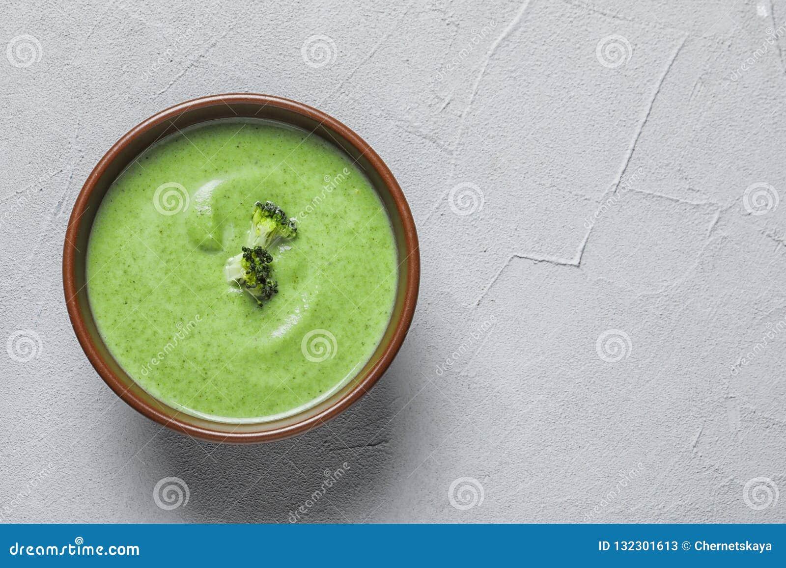 Sopa del detox de las verduras frescas hecha del bróculi en plato en la tabla, visión superior