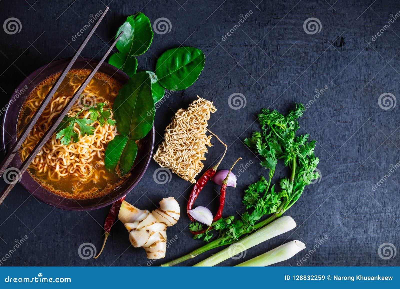 Sopa e vegetais de macarronetes imediatos picante em um fundo preto