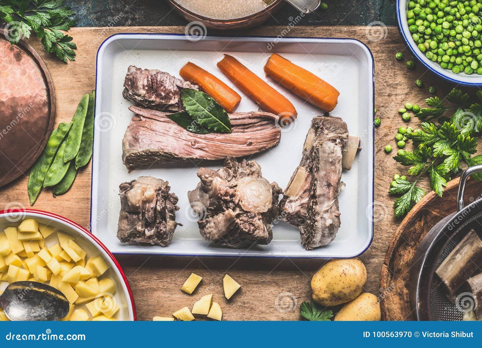Sopa que cocina la preparación con la carne cocinada, las verduras, las patatas y los guisantes verdes en la tabla de cocina rúst