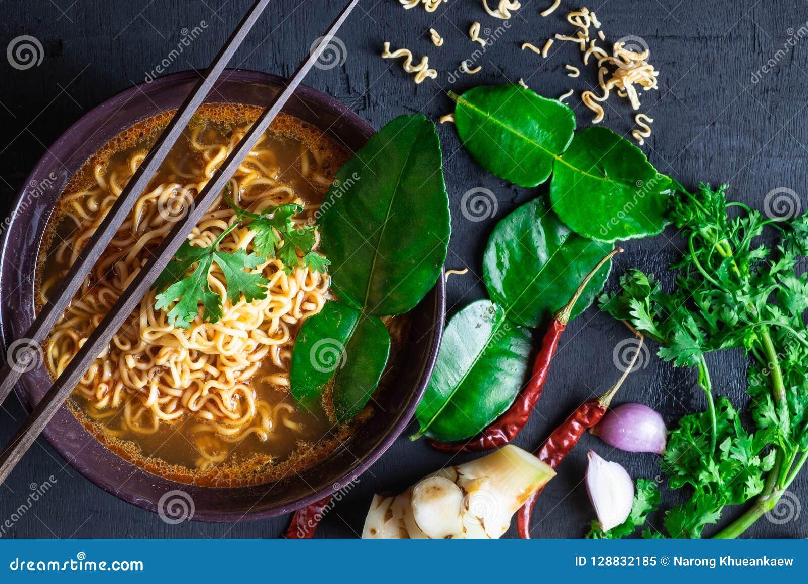 Sopa y verduras de tallarines inmediatos picante en un fondo negro
