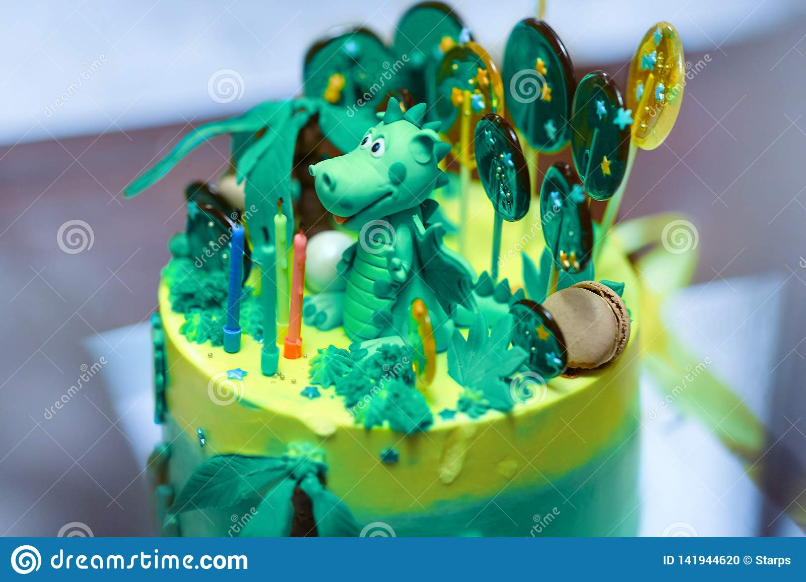 Sophisticatedly designed homemade Birthday cake with Dinosaur figure between the sweeties, green and yellow colors.