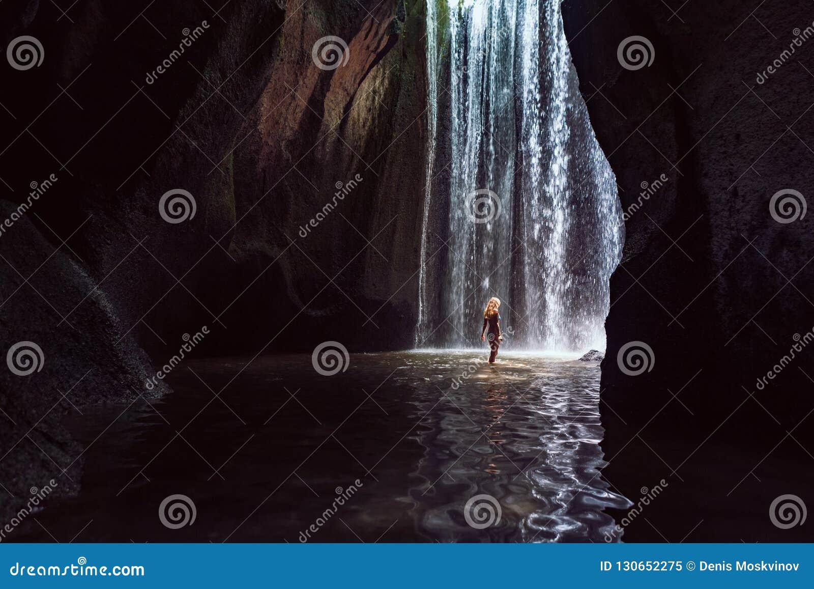 Soporte de la mujer debajo de la cascada de la cueva