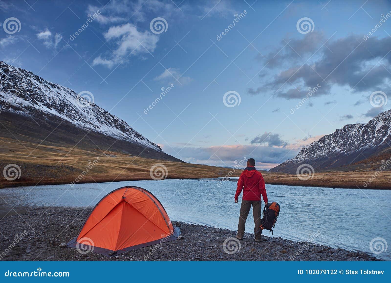 Soporte del caminante en acampar en las montañas durante primavera