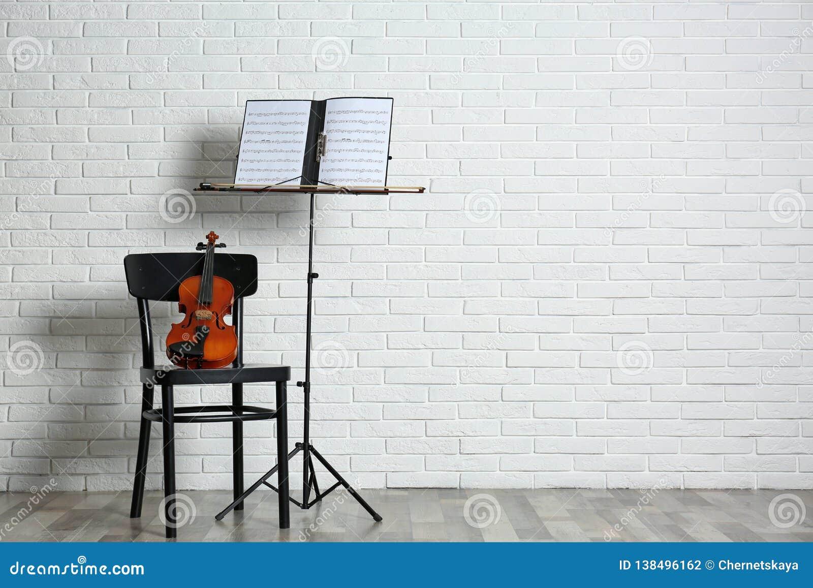 Soporte del violín, de la silla y de la nota con las hojas de música cerca de la pared de ladrillo