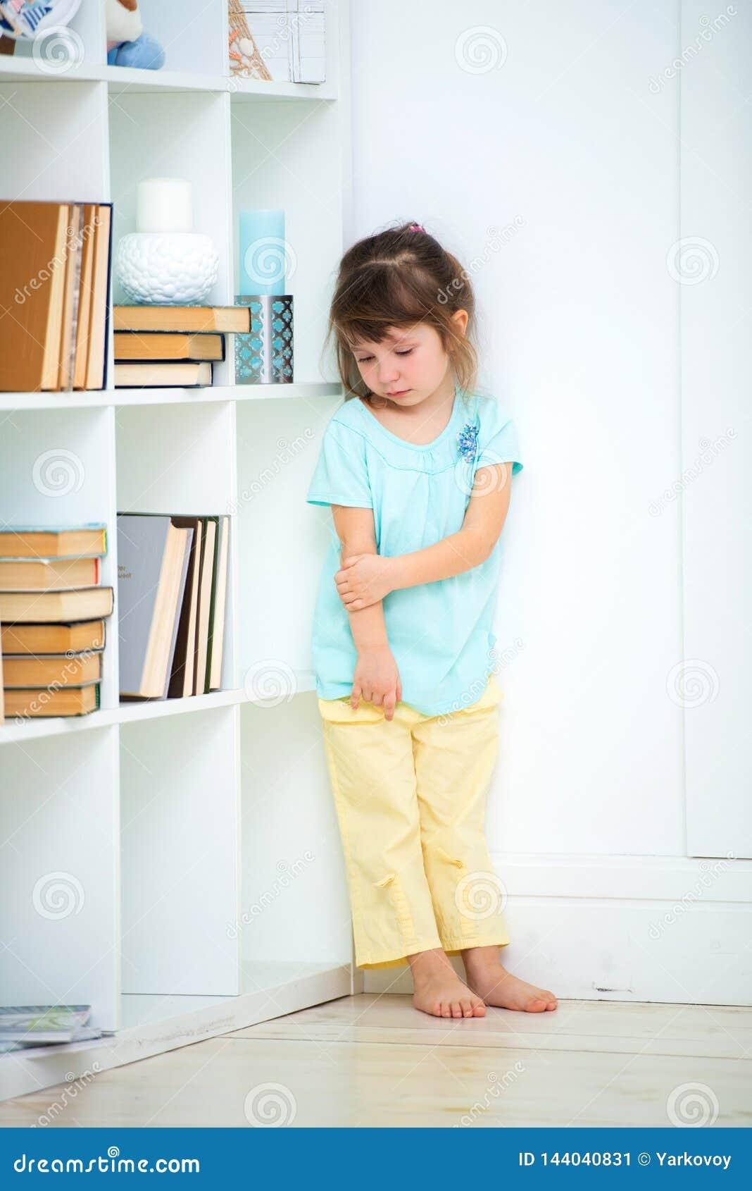 Soportes delincuentes tristes pequeños de una muchacha castigados en la esquina Vinos y castigo de niños