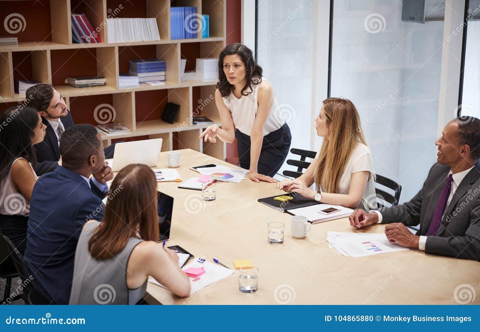 Soportes femeninos del encargado que se dirigen al equipo en la reunión de la sala de reunión