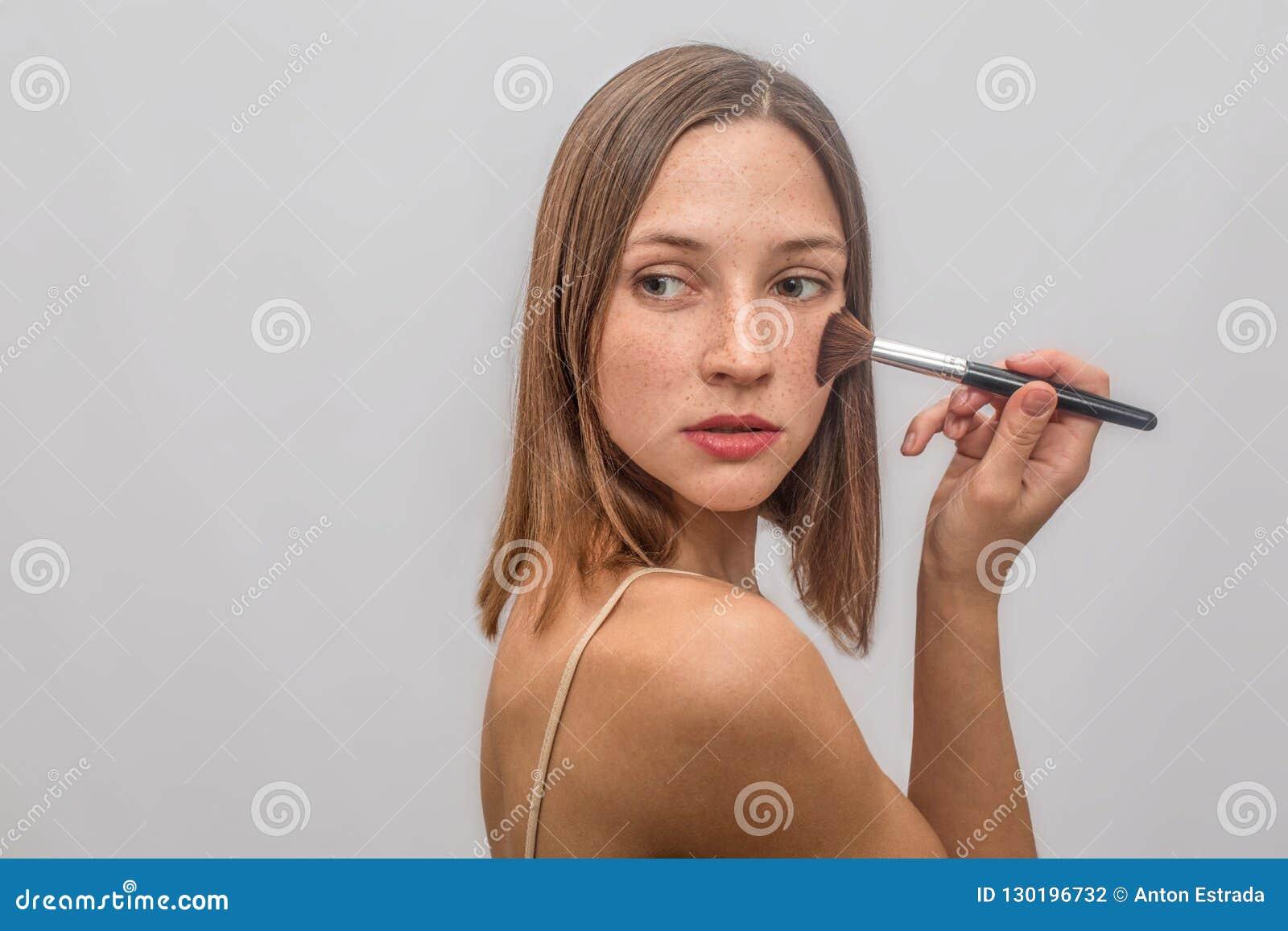 Soportes hermosos y agradables y actitudes de la mujer joven Ella pone compone con el cepillo en sus polluelos Ella mira a la izq