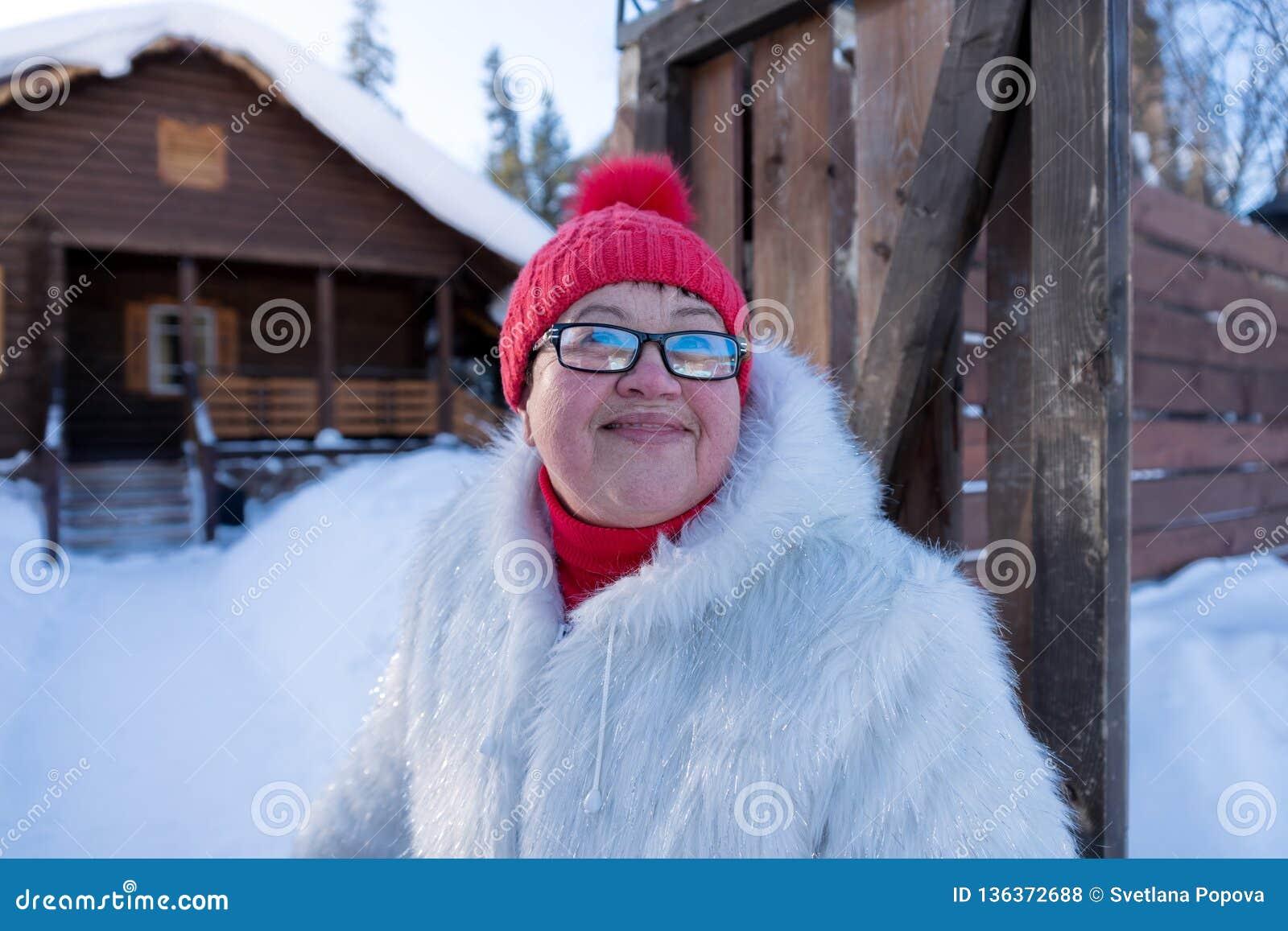 Soportes y sonrisas alegres de la mujer feliz en la entrada de la casa de madera del pueblo