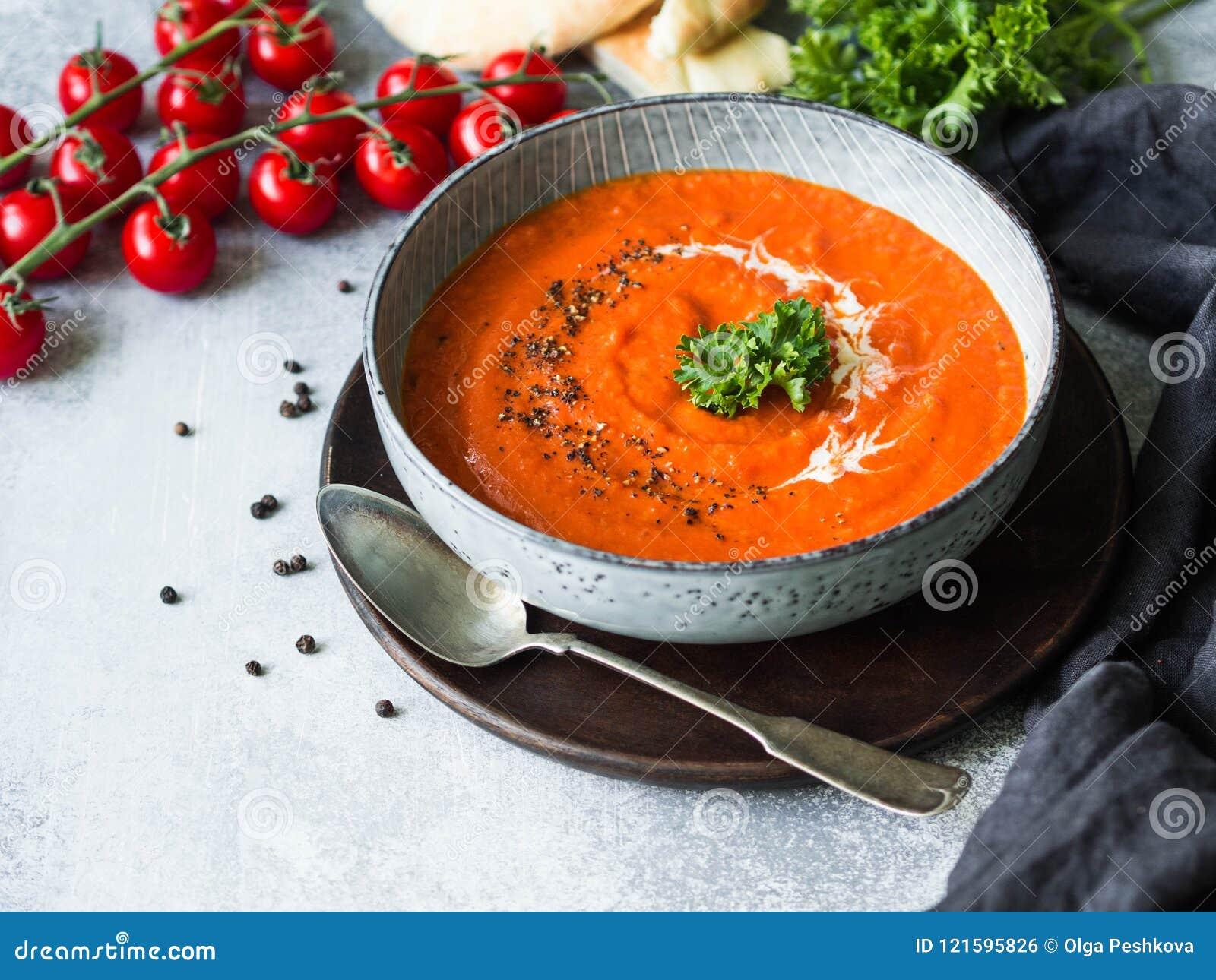 Soppa eller puré för tomat kräm- med ny lockig persilja, kräm och svartjordpeppar Blå platta med soppa på en grå bakgrund snut